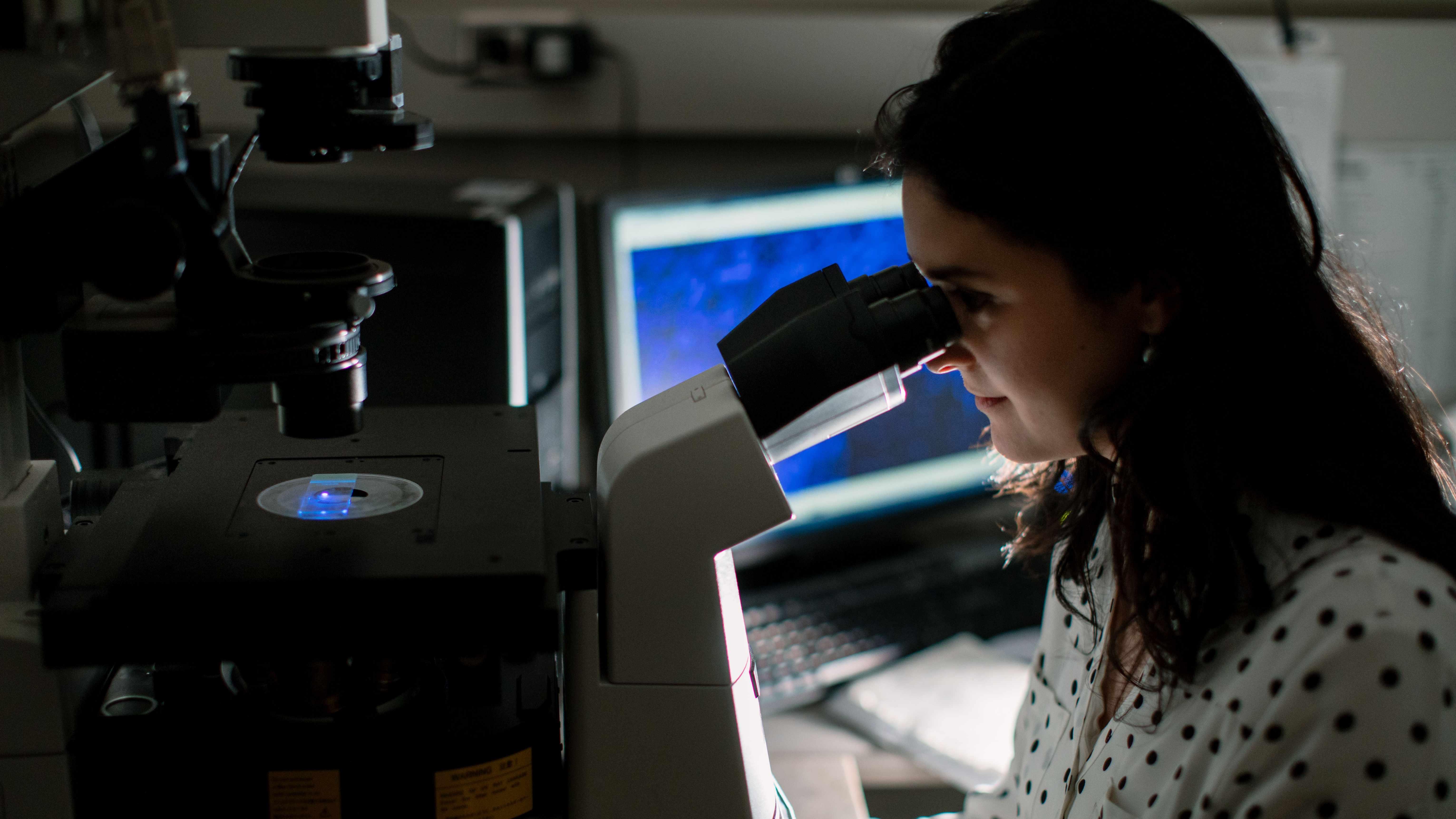 Una investigadora observa una lámina bajo el microscopio.