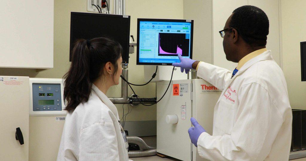 El Dr. Abba Zubair y una colega en la investigación sobre células madre conversan en el laboratorio mientras observan la pantalla de un computador