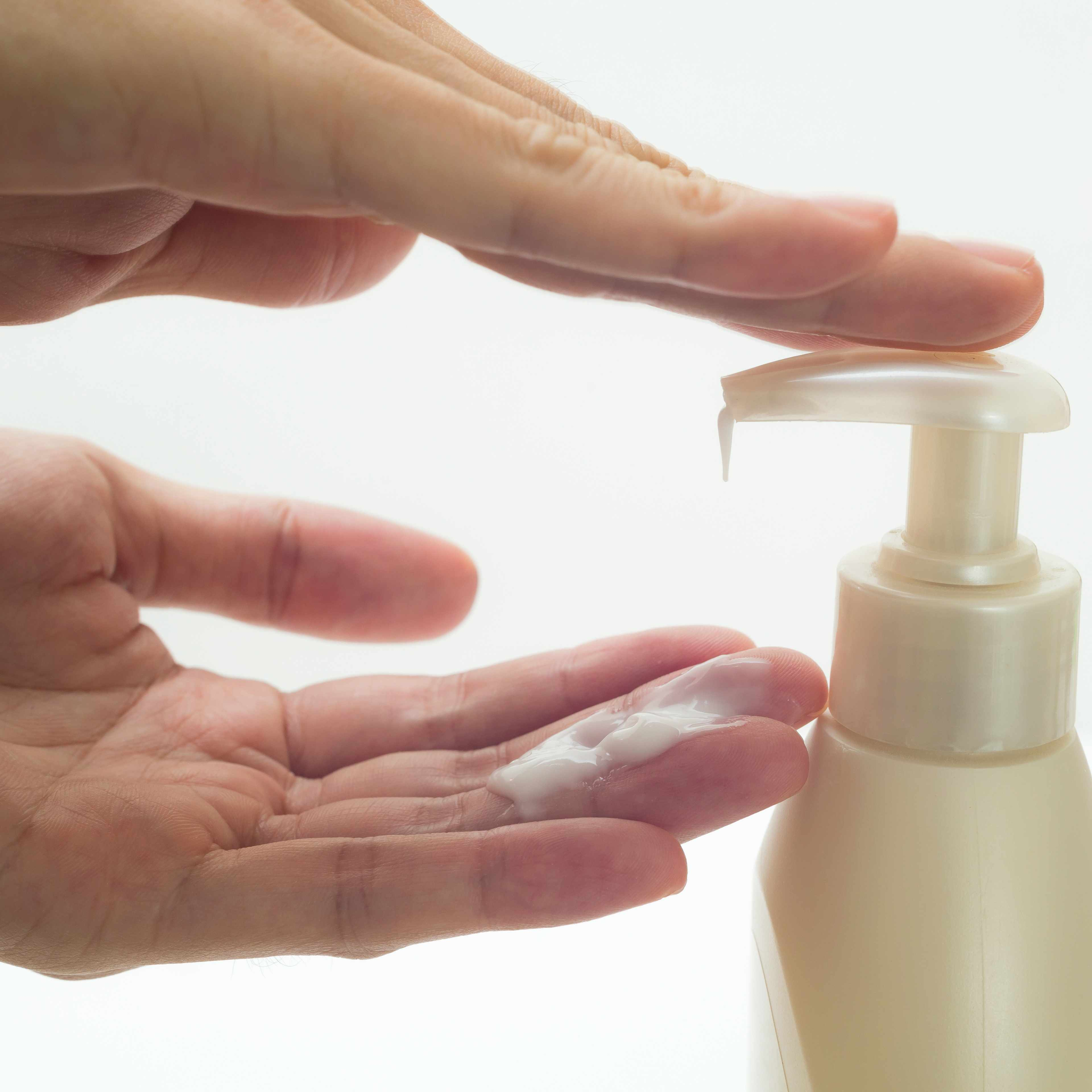 a close-up of two hands pumping lotion from a bottle