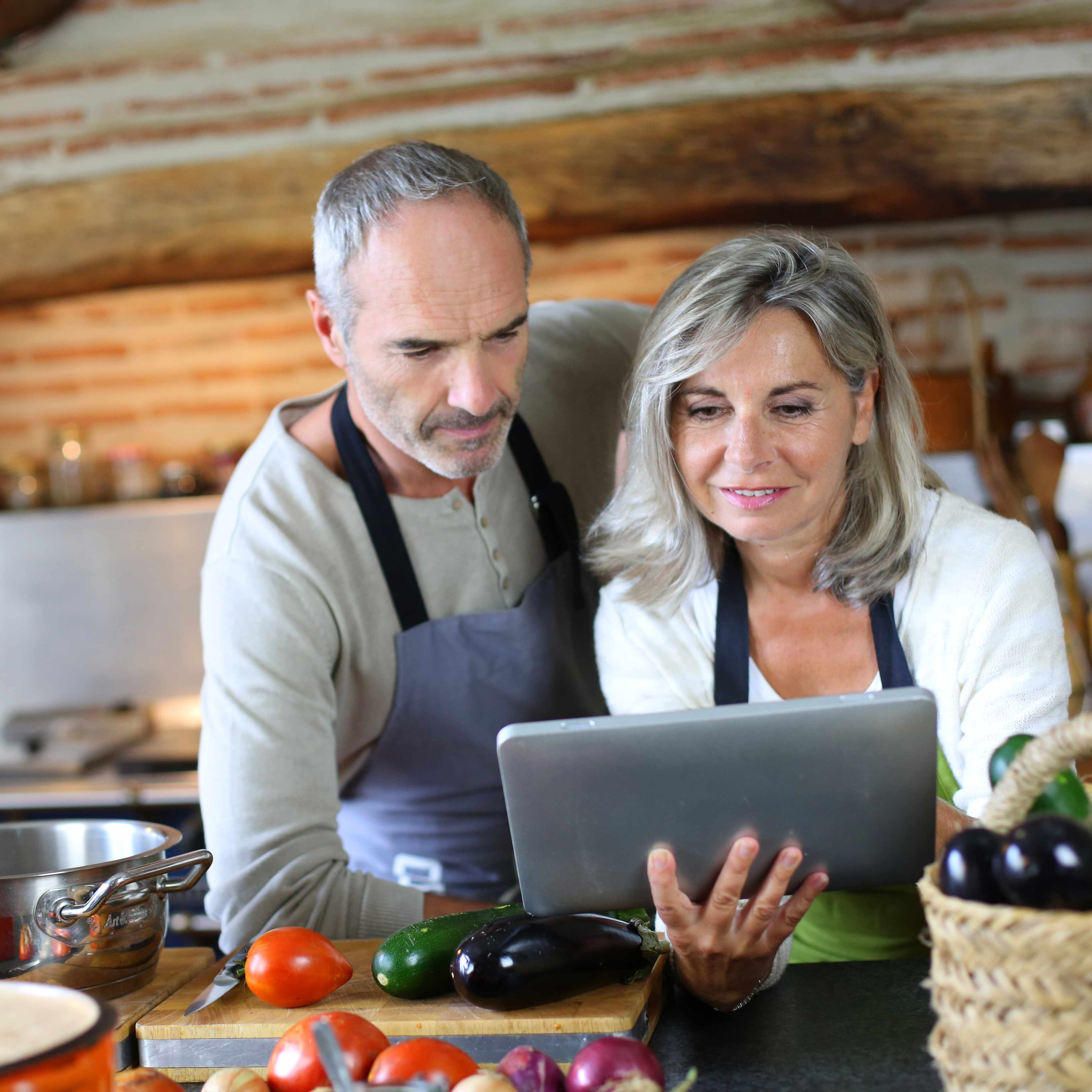 a middle-aged couple in a kitchen, looking at a laptop and preparing food