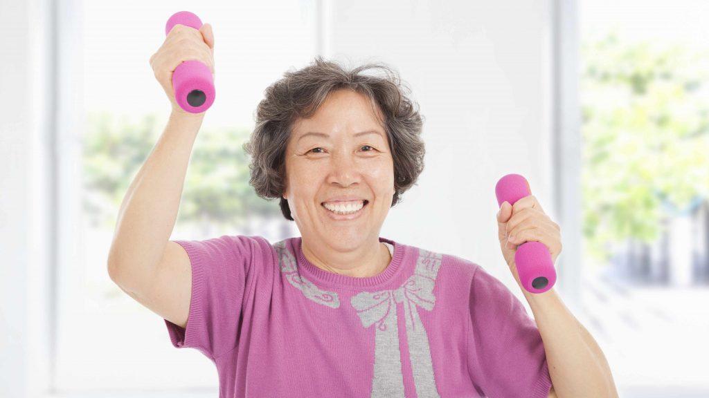 Una mujer mayor sonríe mientras hace ejercicios con pesas de mano