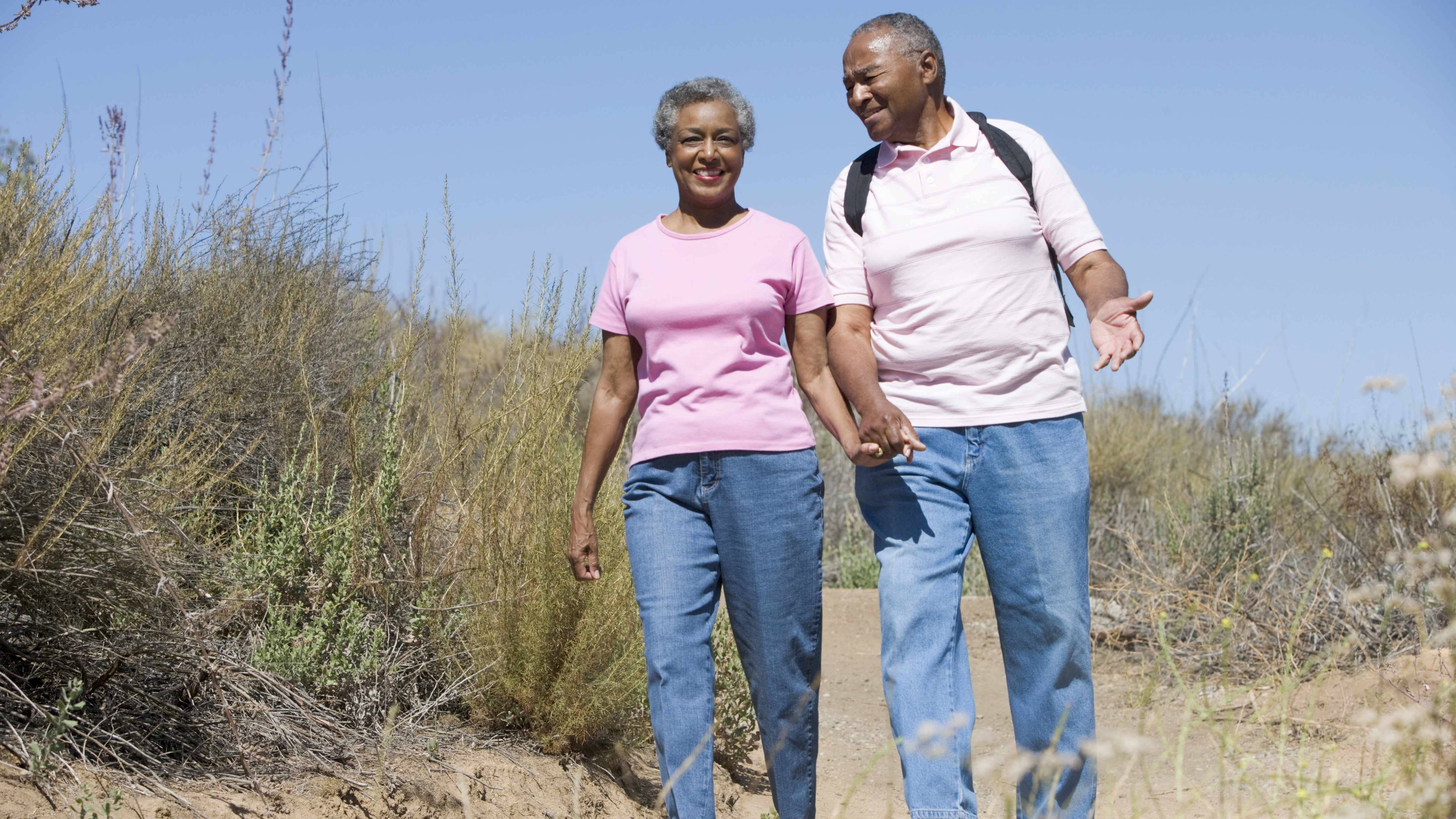 an African-American middle-aged couple holding hands and walking, exercising on the beach