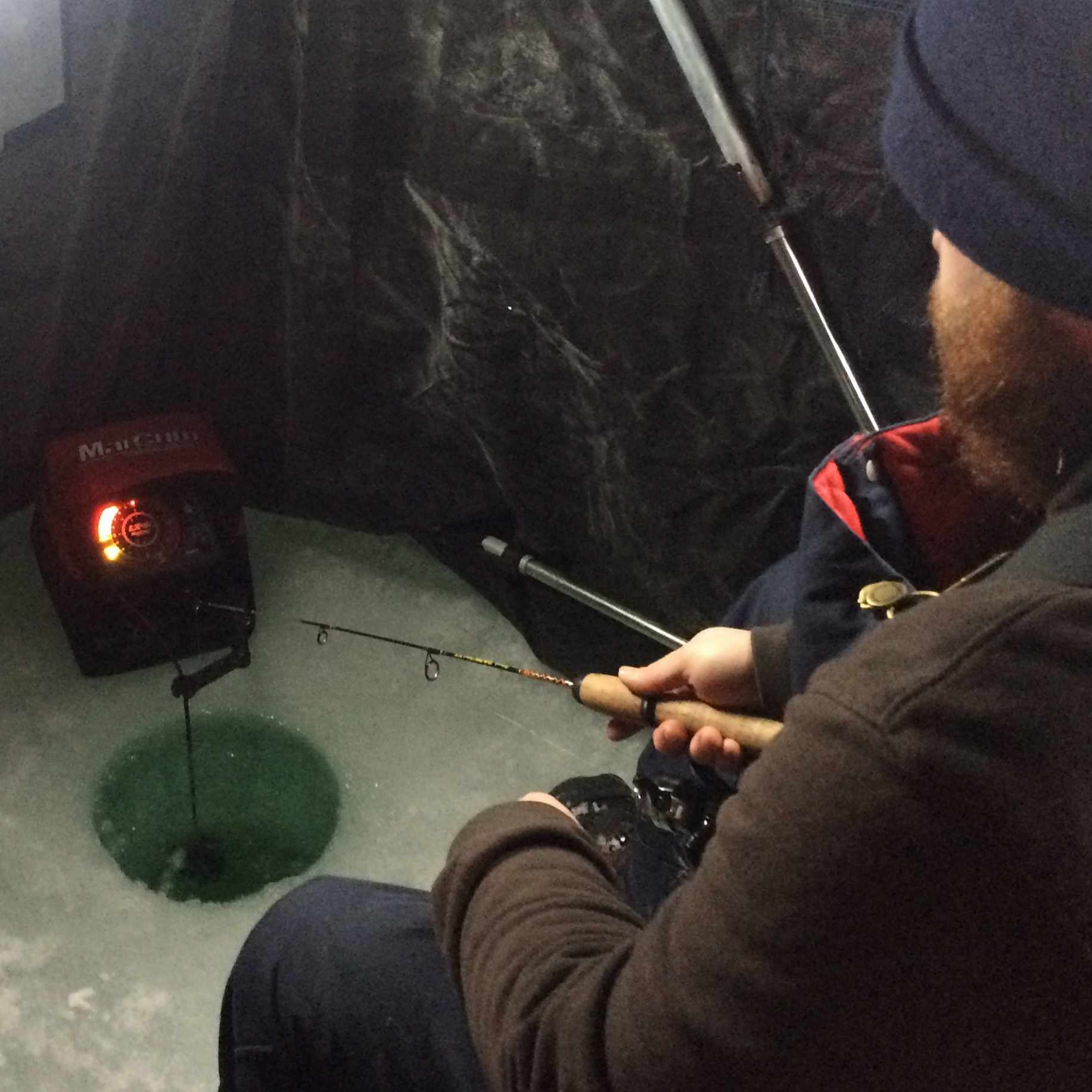 ice fisherman in an ice house with fishing line in hole