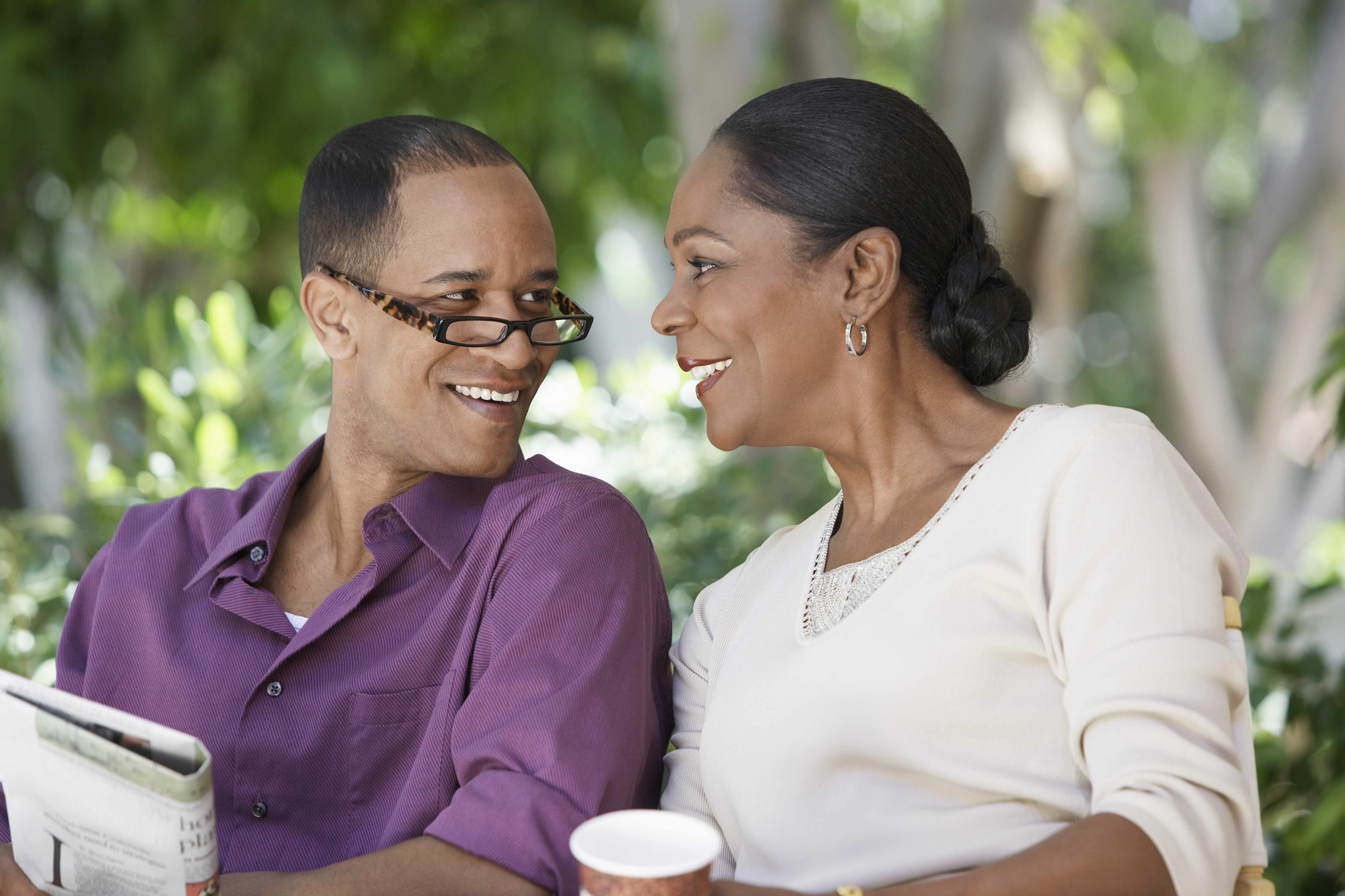 a middle-aged couple sitting outside, looking at one another and smiling