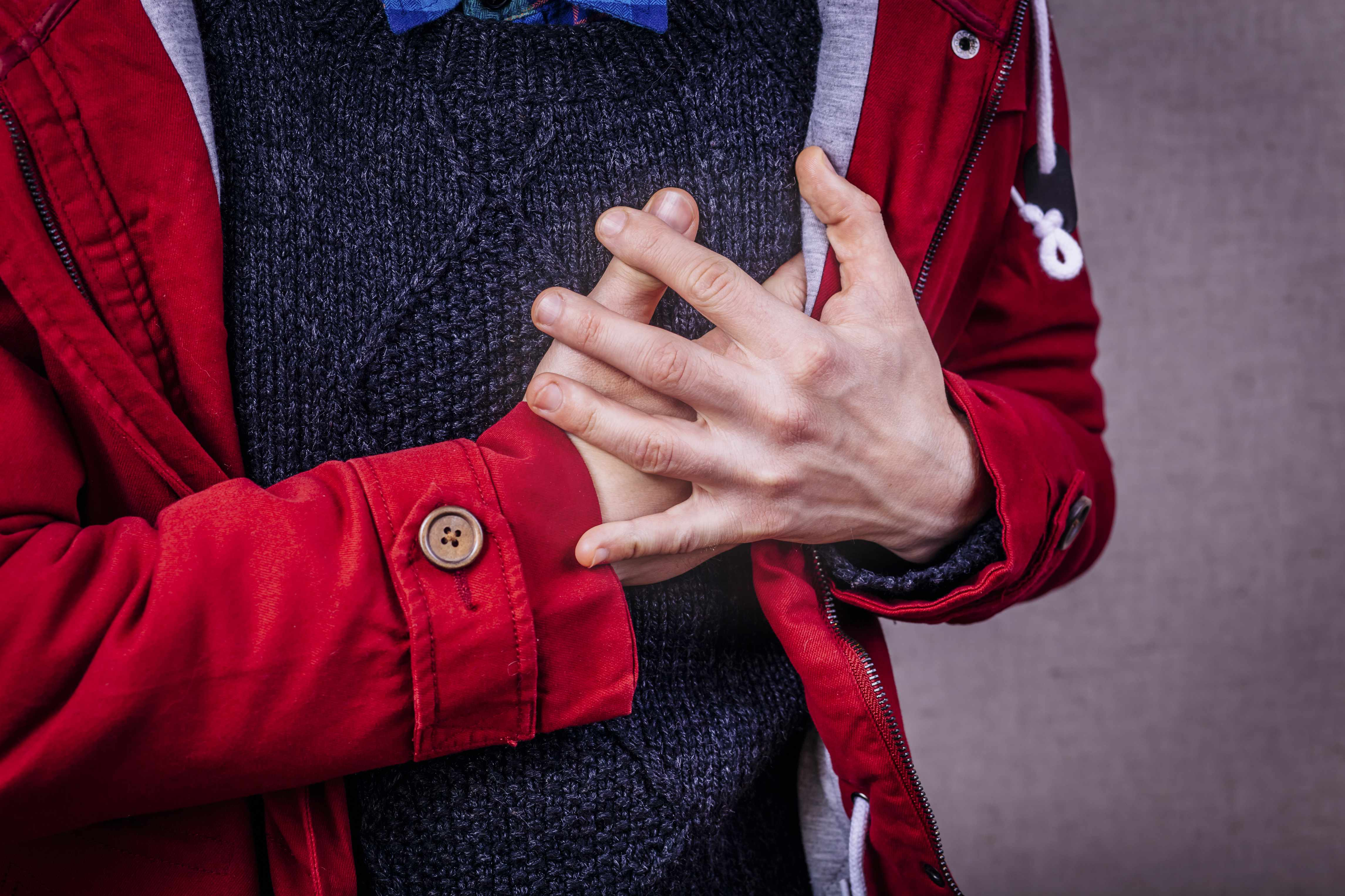 a person in a red coat holding chest with pain, perhaps a heart attack