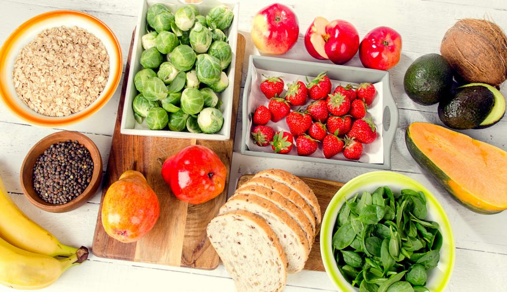 a variety of high-carbohydrate foods in bowls and on wooden surfaces, including fruits, vegetables and grains