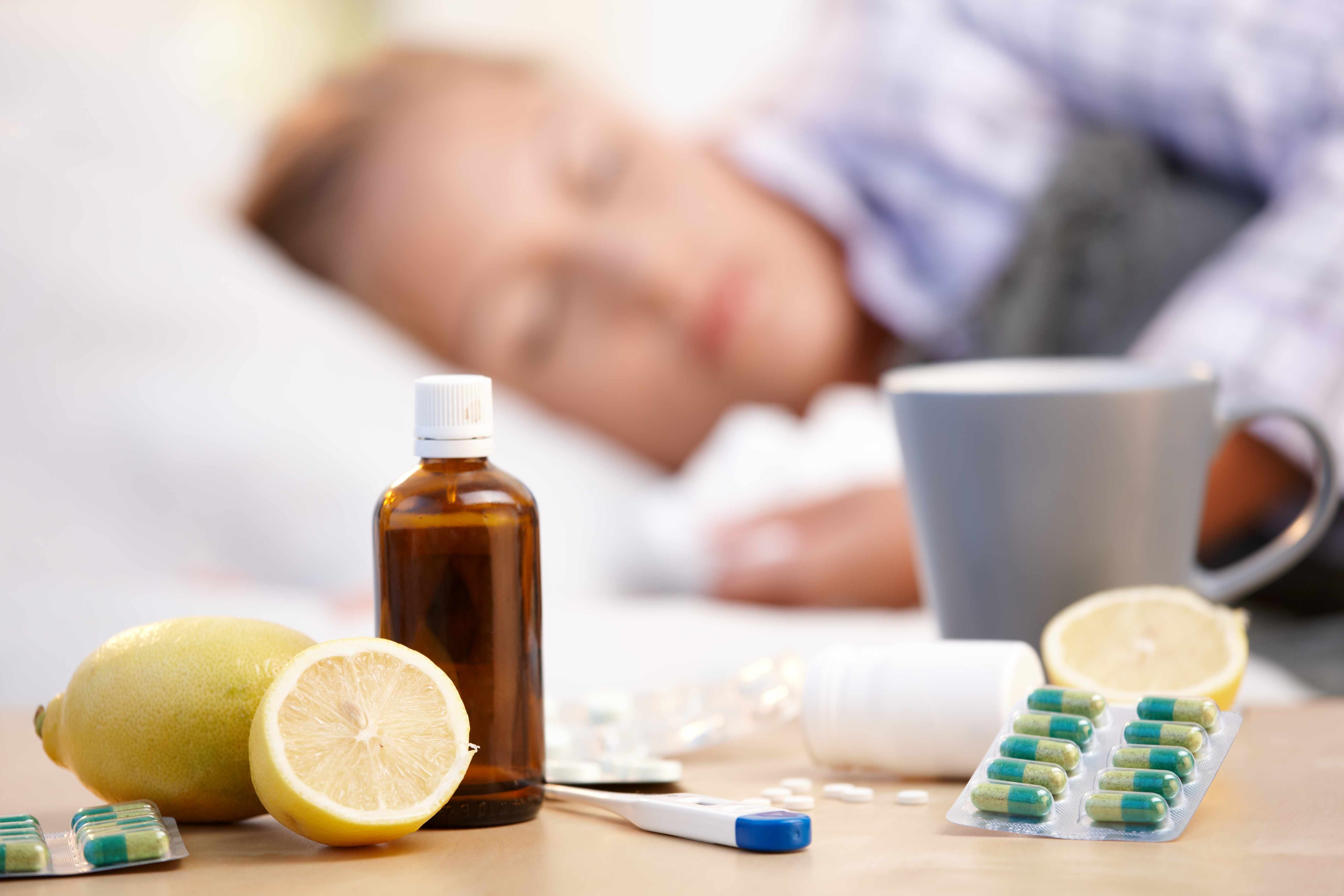 a sick person with a cold or flu, sleeping in bed with medications on the bedside table