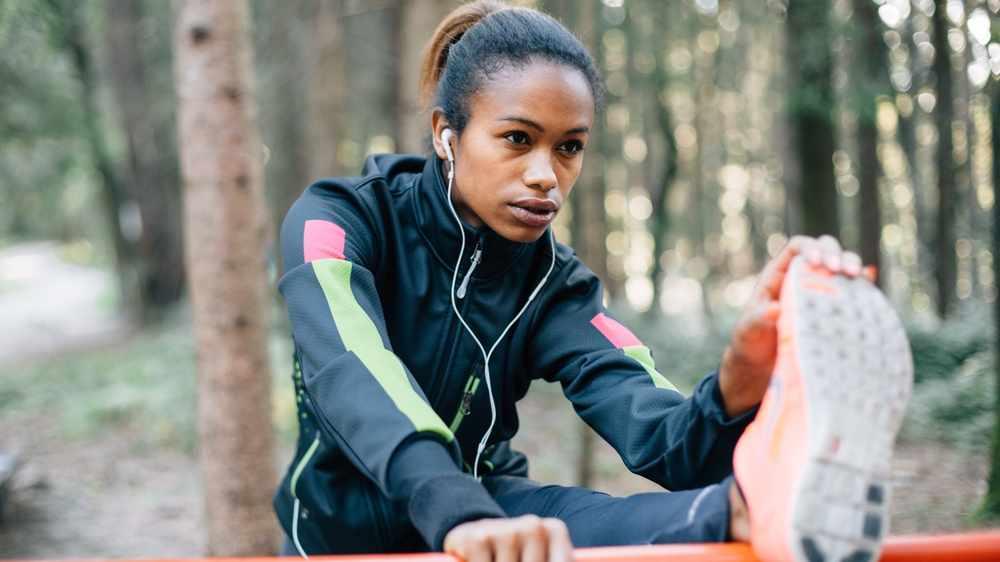Una mujer afroamericana se estira antes de hacer ejercicio