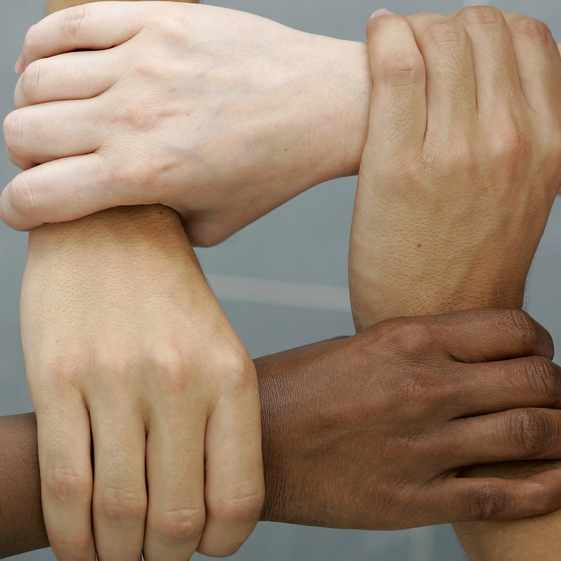 young people of different skin colors linking arms