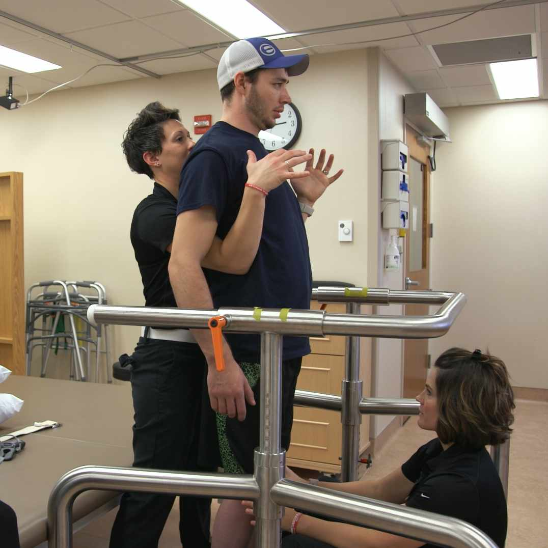 paralyzed patient Jered Chinnock standing in physical therapy room