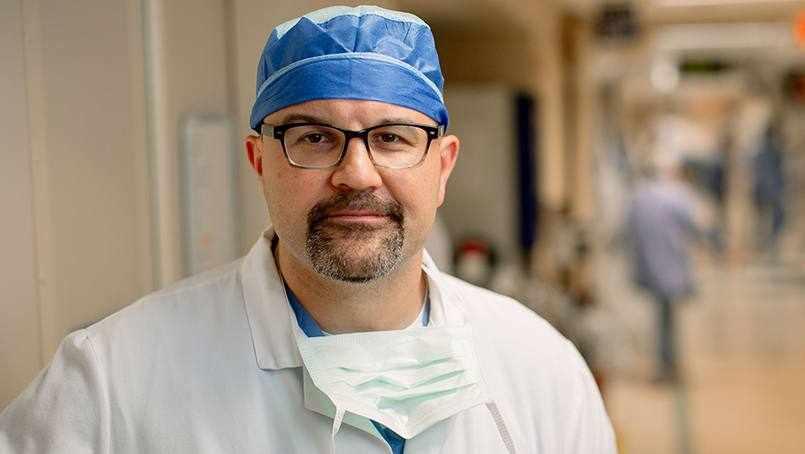 Dr. Mark Truty in surgery scrubs standing in hospital corridor