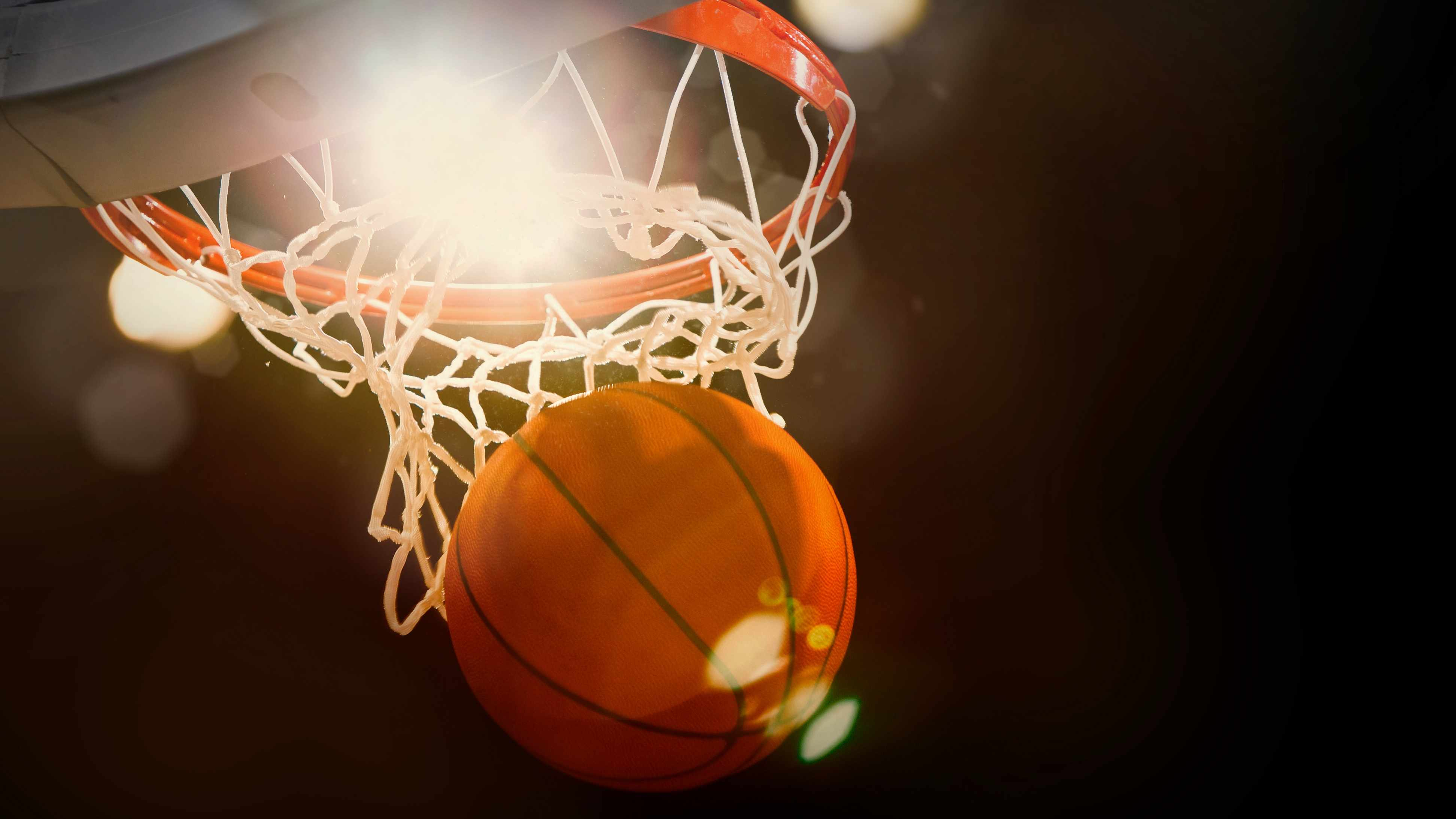 a basketball swooshing through a hoop with bright light in the background