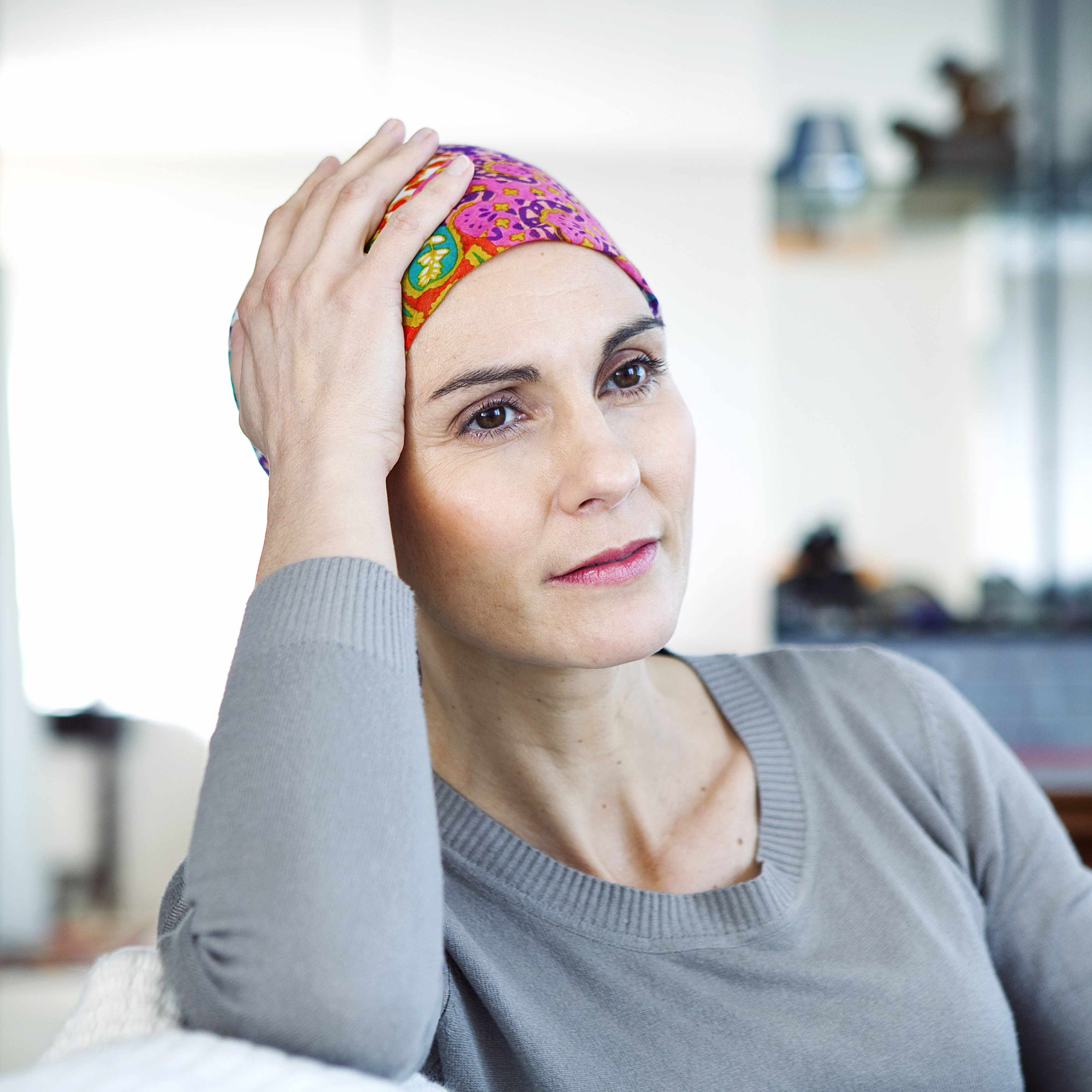 a close-up of a woman in a brightly colored headscarf, looking off into the distance
