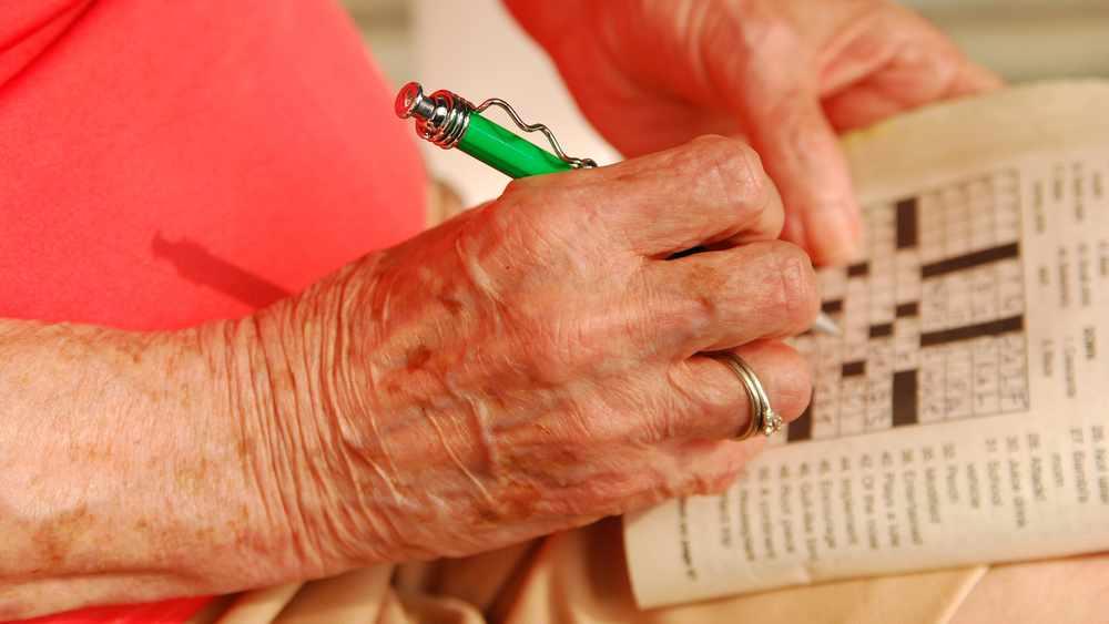 Acercamiento de la mano de una anciana que llena un rompecabezas con una pluma