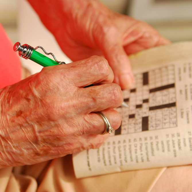 a close-up of an older woman's hand, holding a pen and working on a crossword puzzle