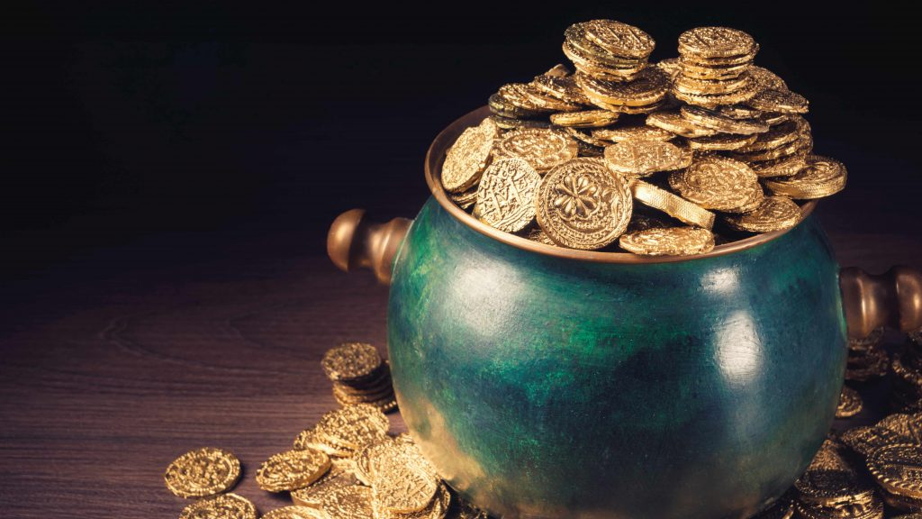 a green pot full of gold coins sitting on a table