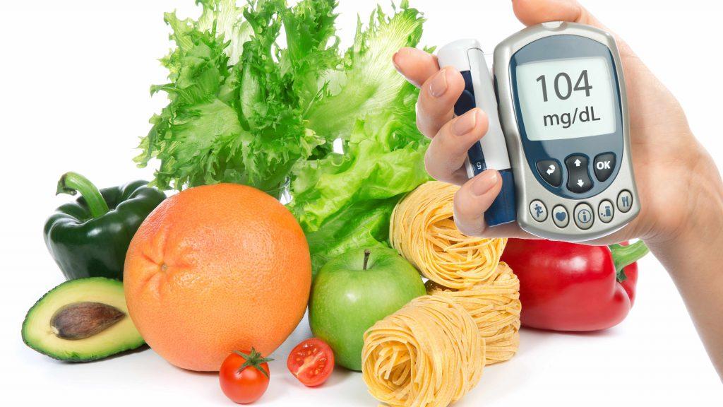 Una mano sostiene un glucómetro frente a varias frutas, verduras y fideos