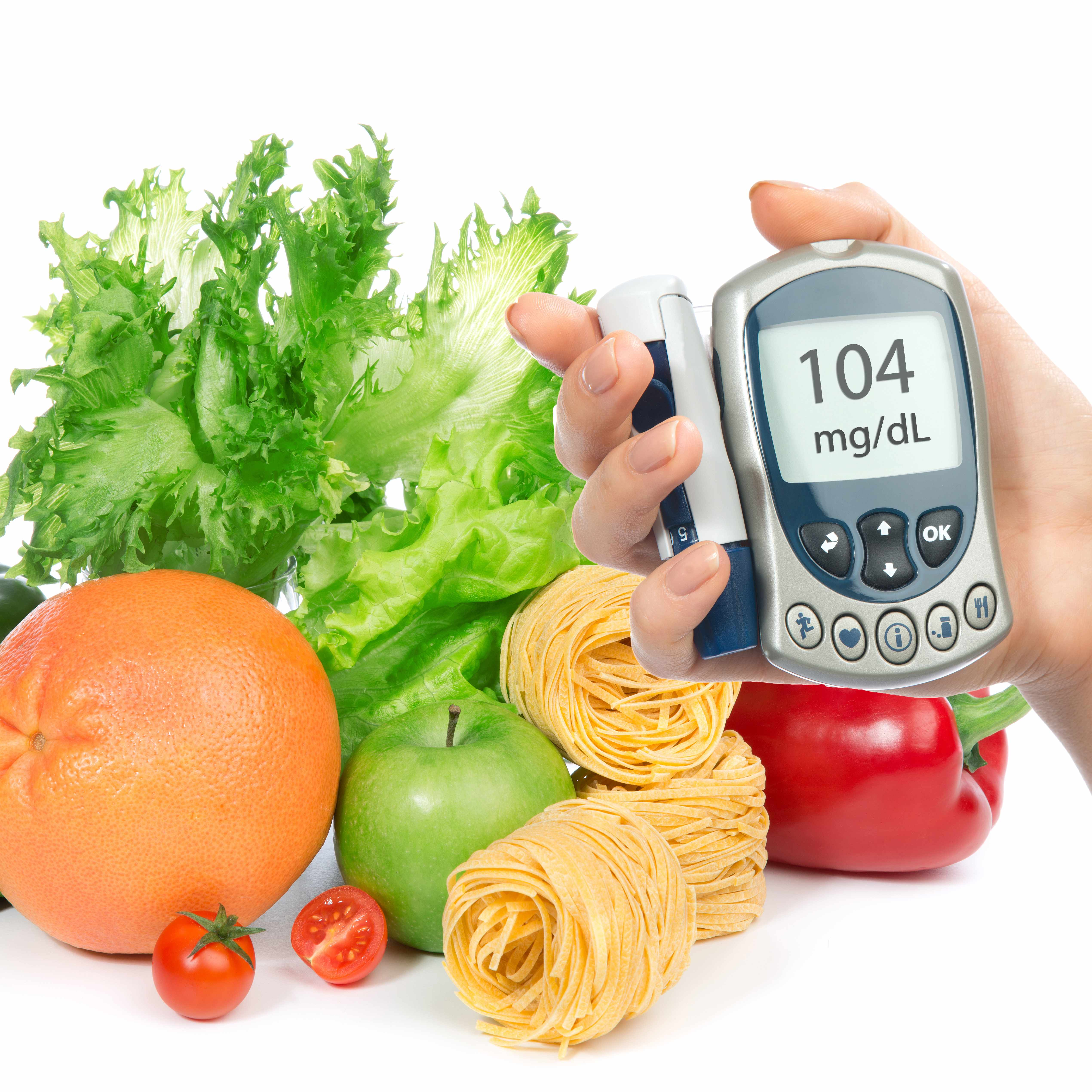 a hand holding a glucose meter in front of a variety of fruits, vegetables and pasta