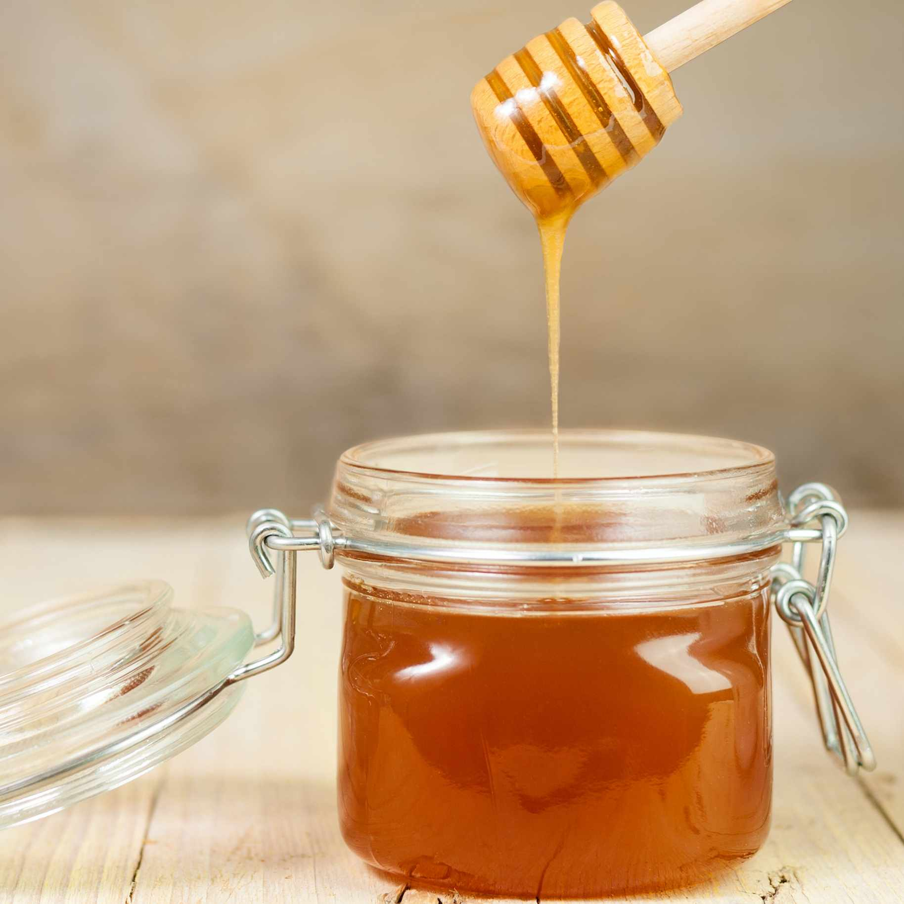 a jar of honey on a table with a wooden spindle