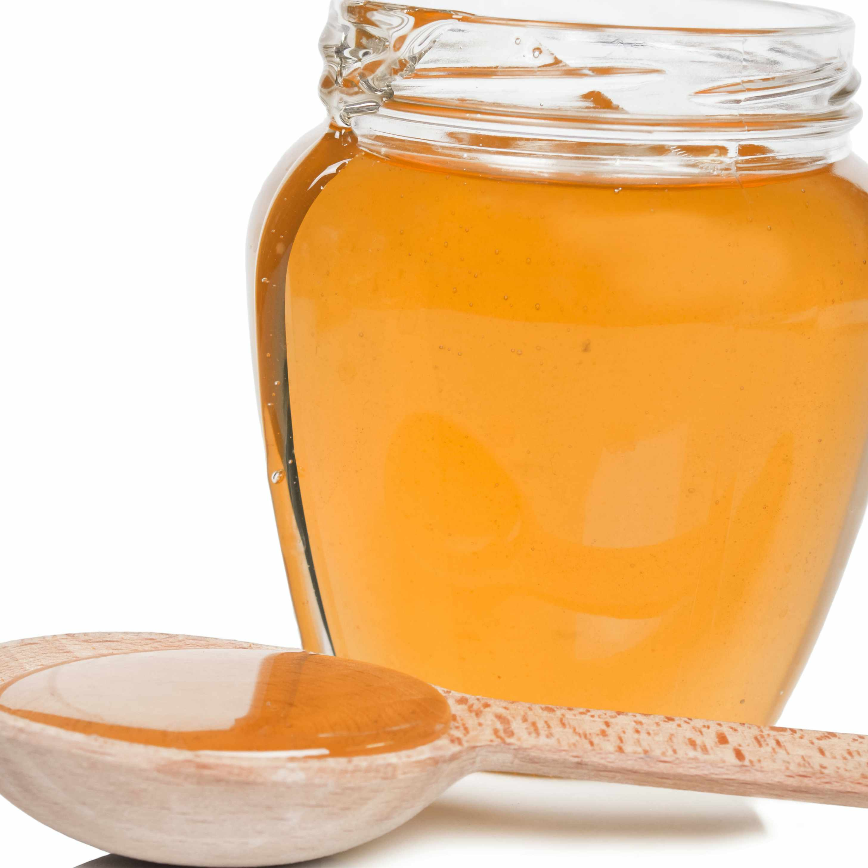 a jar of honey on a table with a wooden spoon