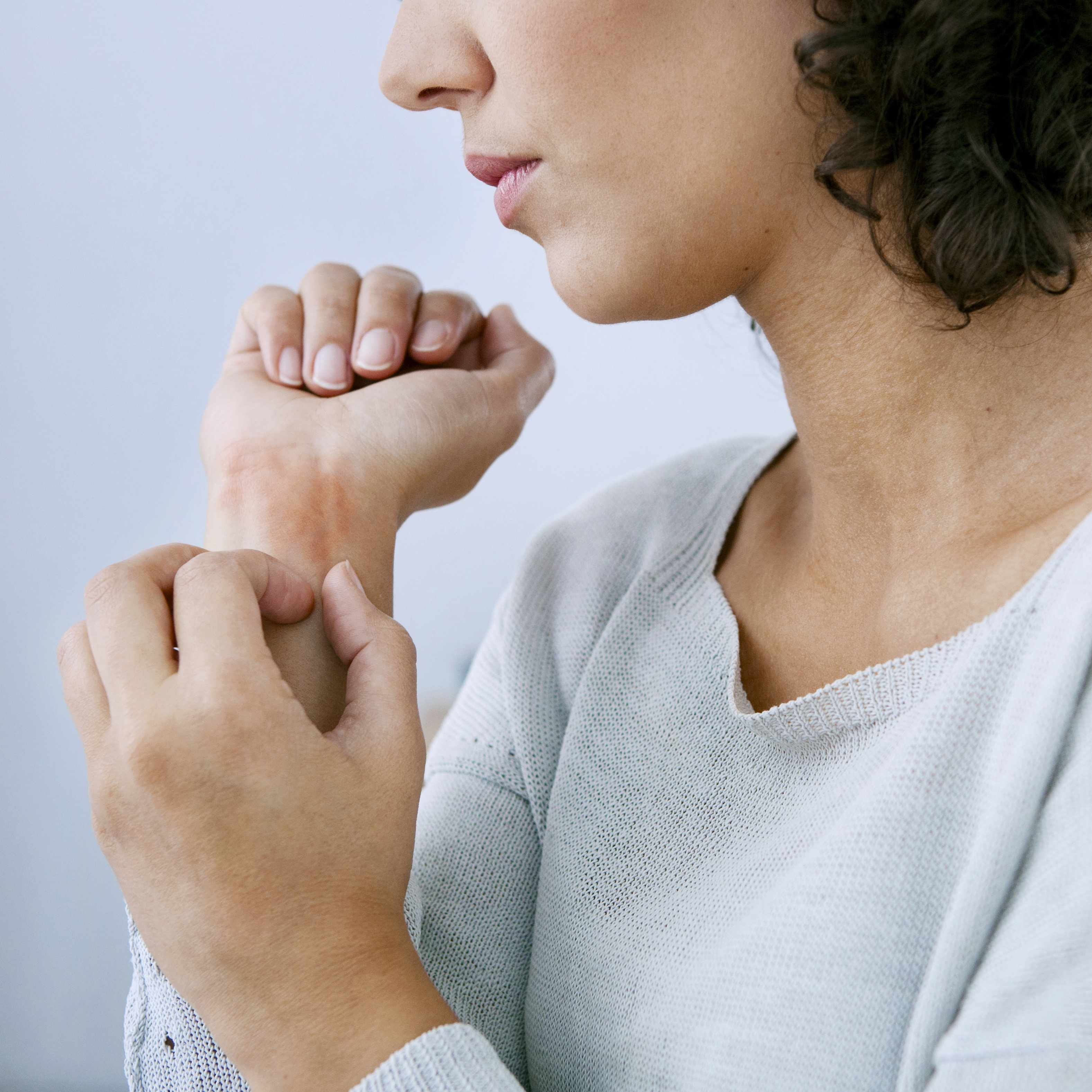 a woman scratching her itchy skin rash, hives