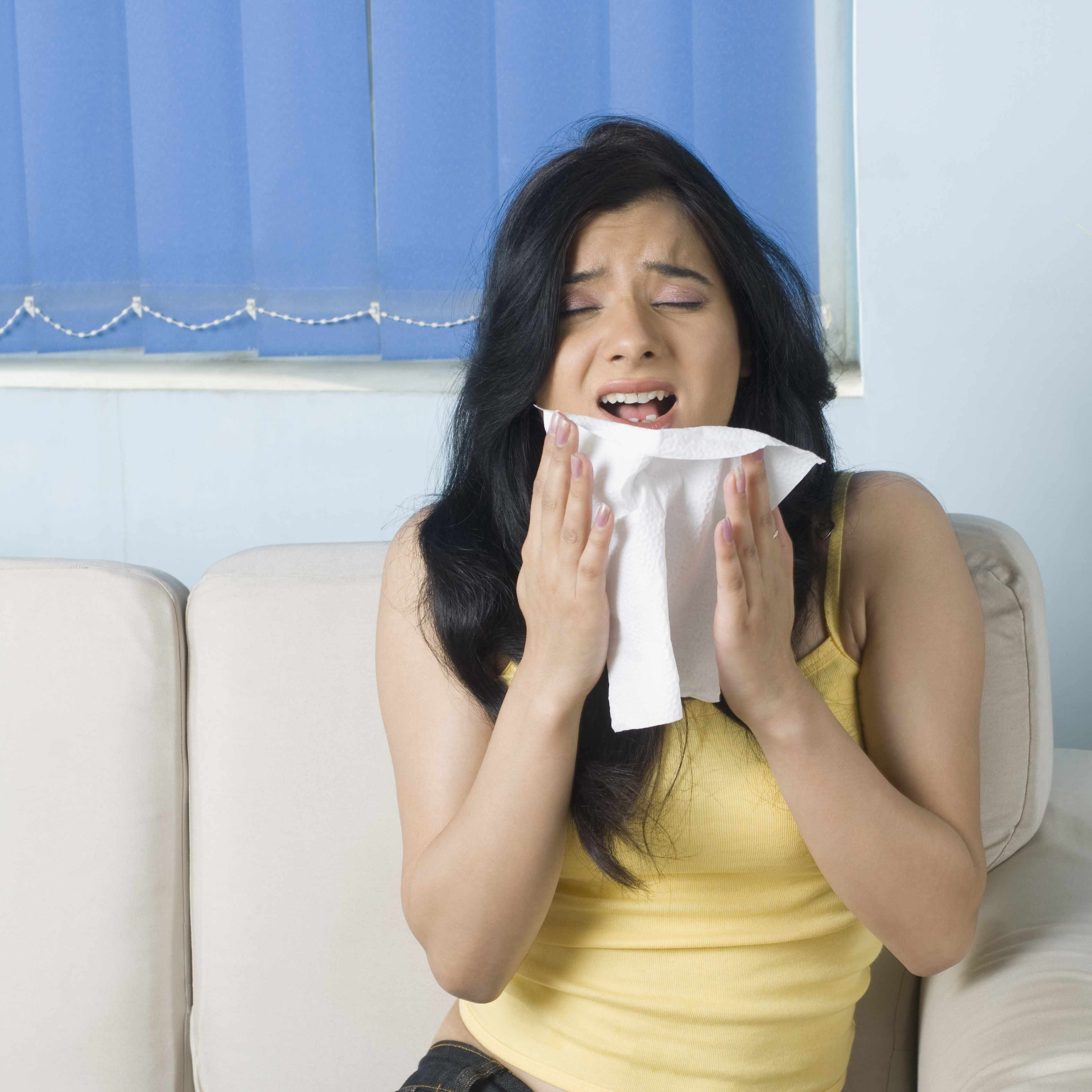 a young woman sitting on a couch, just about to sneeze