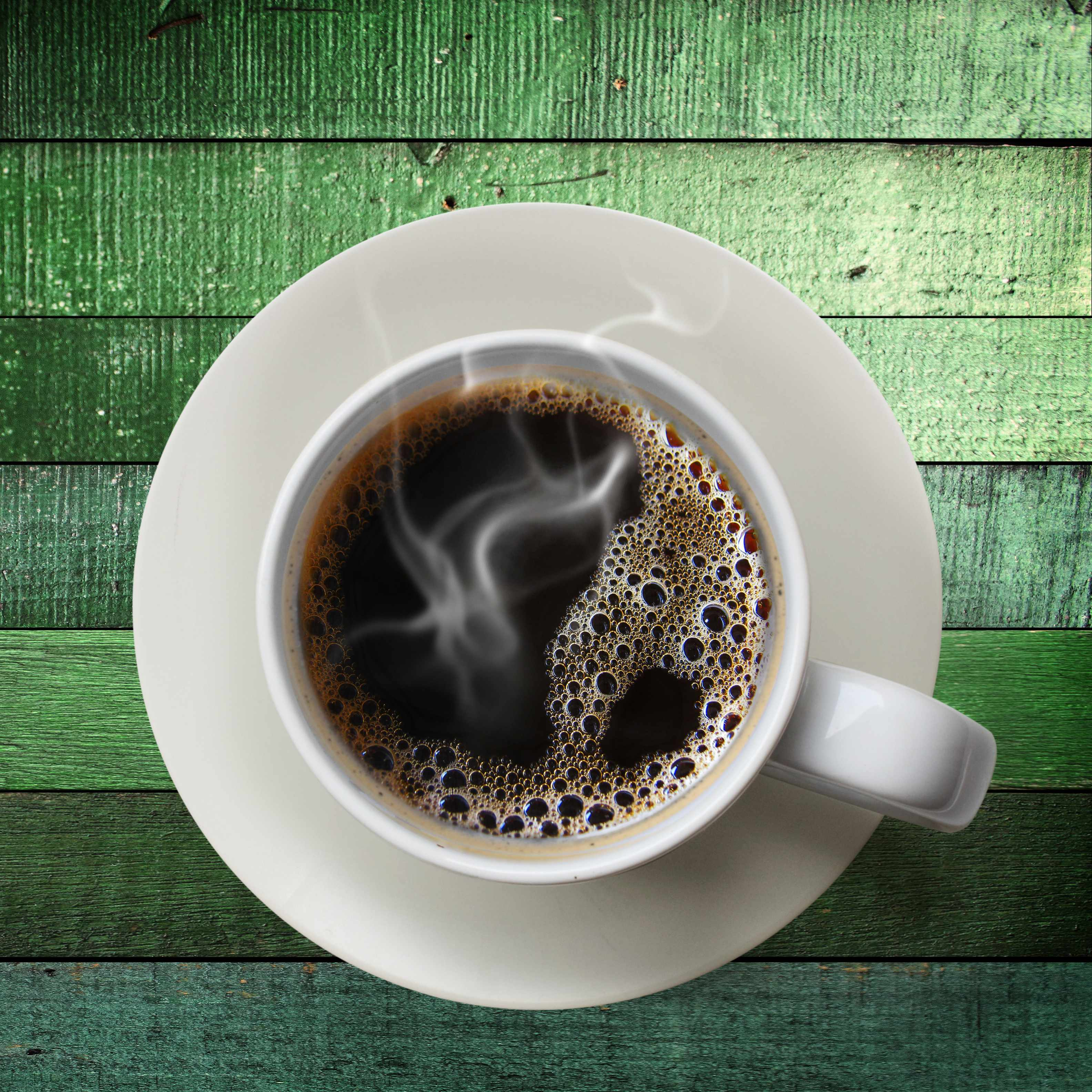 an overhead view of a single cup of steaming coffee on a green wooden surface