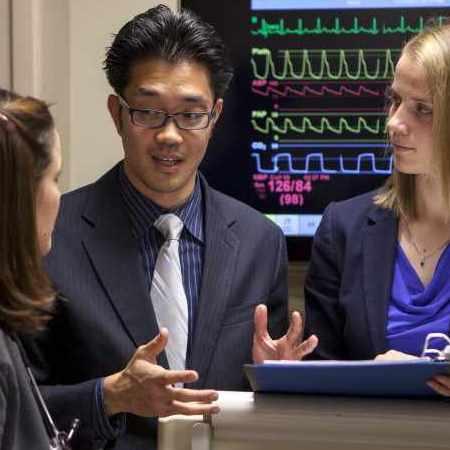 medical students consulting near EKG machine