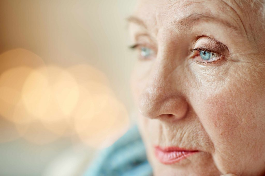 a close-up of an older woman's face, looking away to the side