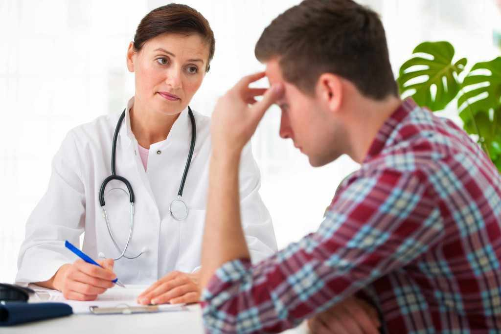 young man with female doctor in conversation about illness