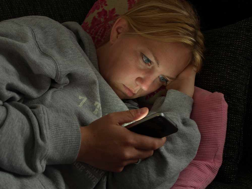 A woman is browsing smartphone cell phone at night in bed