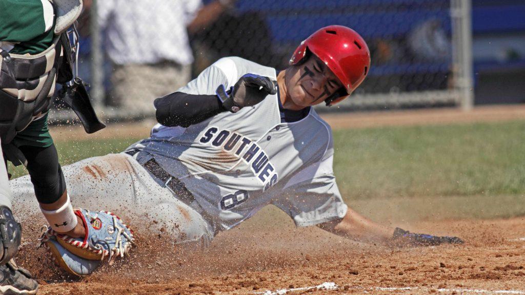 un jugador de béisbol deslizándose hacia una base en el campo