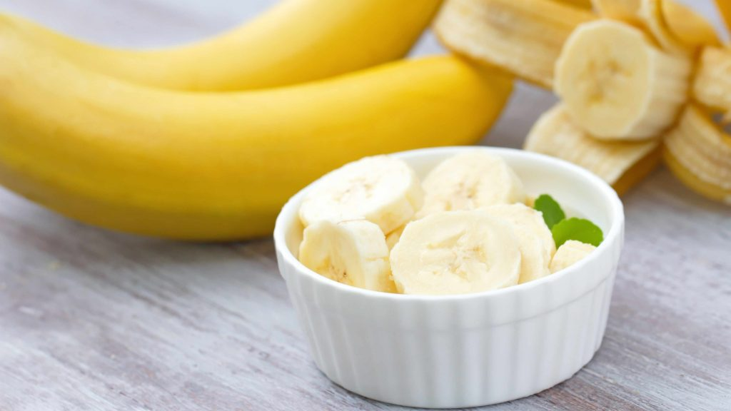 a bunch of bananas on a table and sliced bananas in a cup