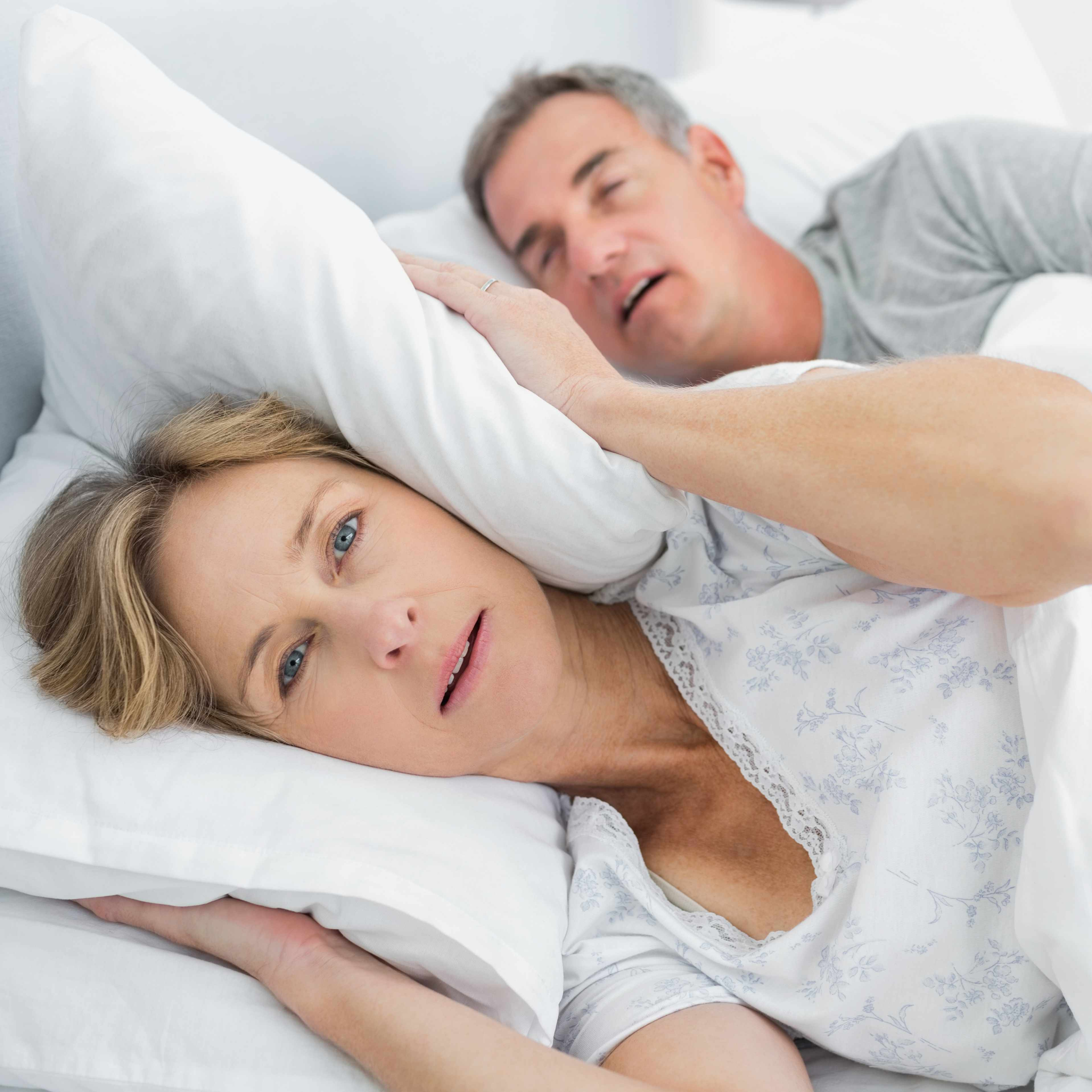 a middle-aged couple in bed with man snoring and woman covering her ears with a pillow