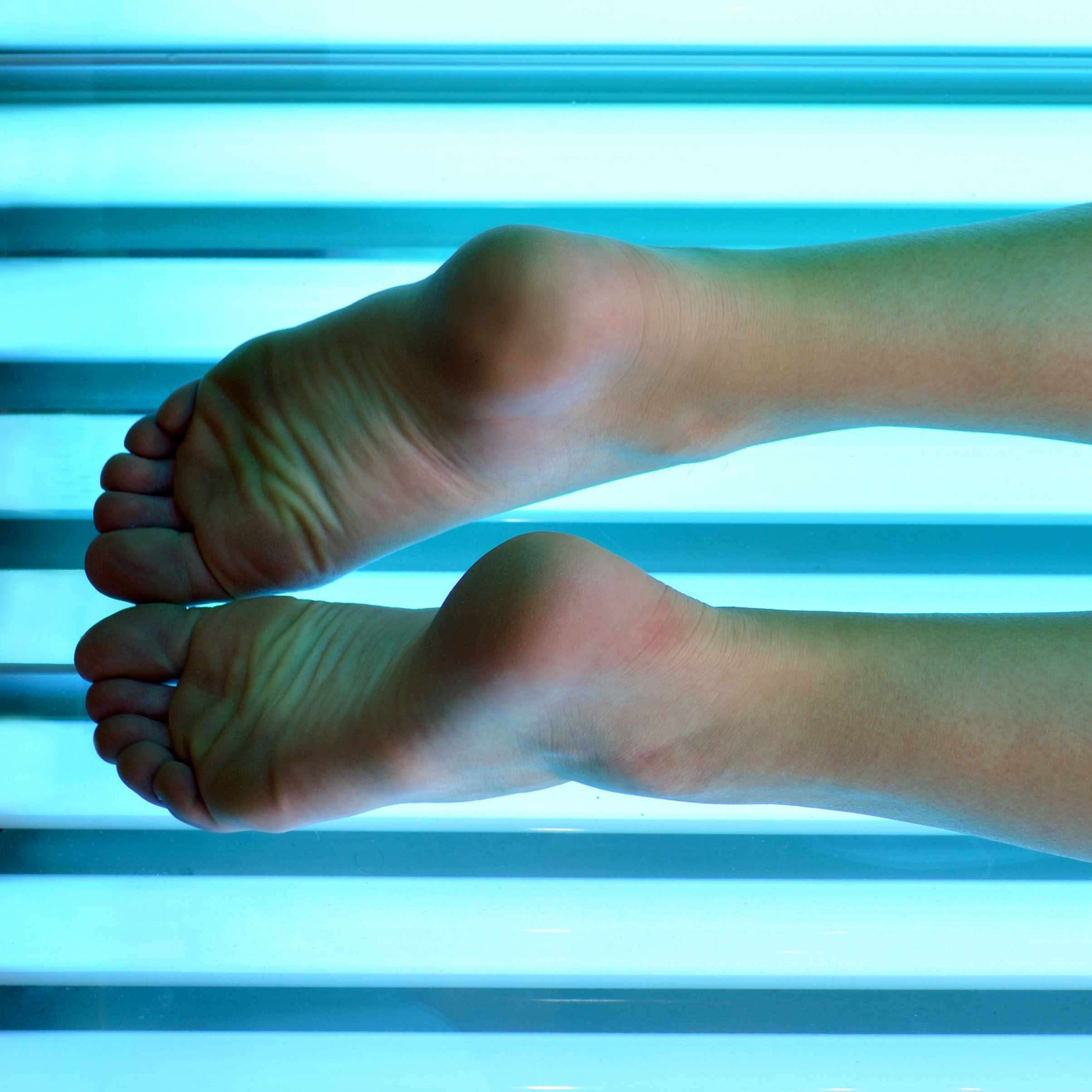 a person's legs resting inside a tanning bed with bright lights on