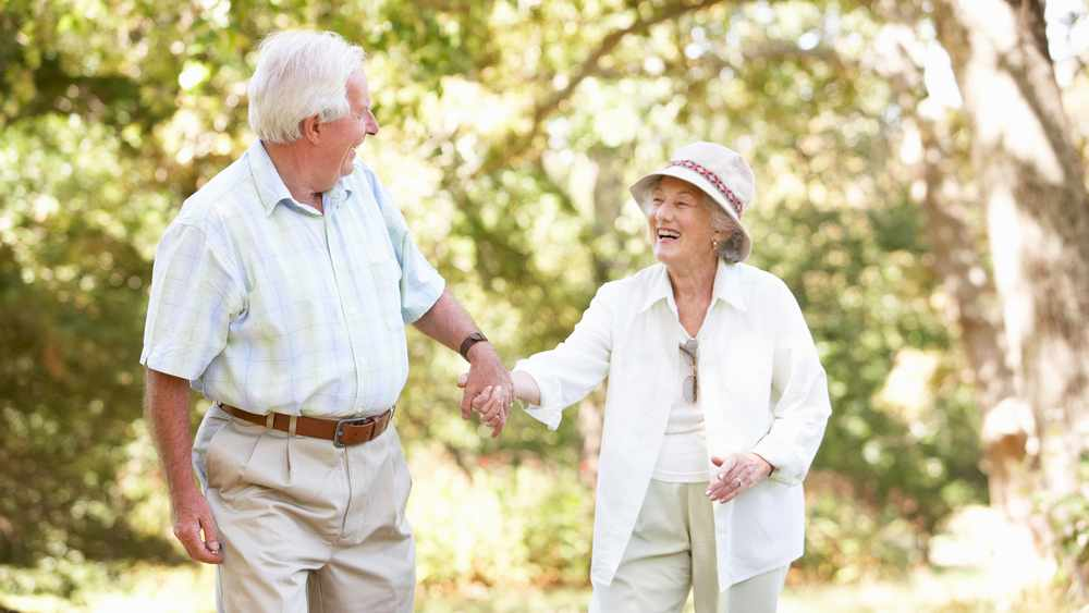 a smiling older couple, holding hands and walking outdoors