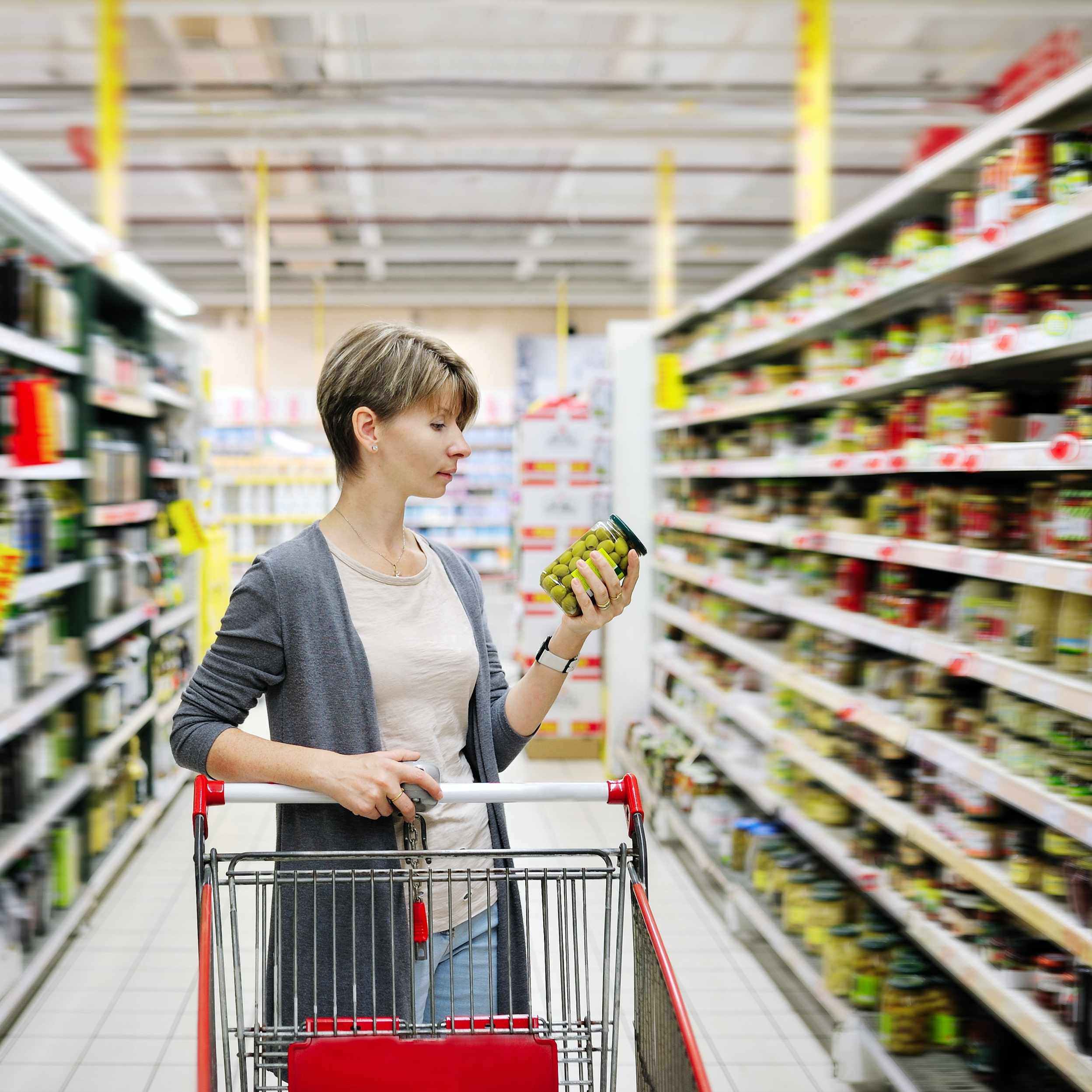 a young woman pushing a shopping cart in a grocery store reading a food label