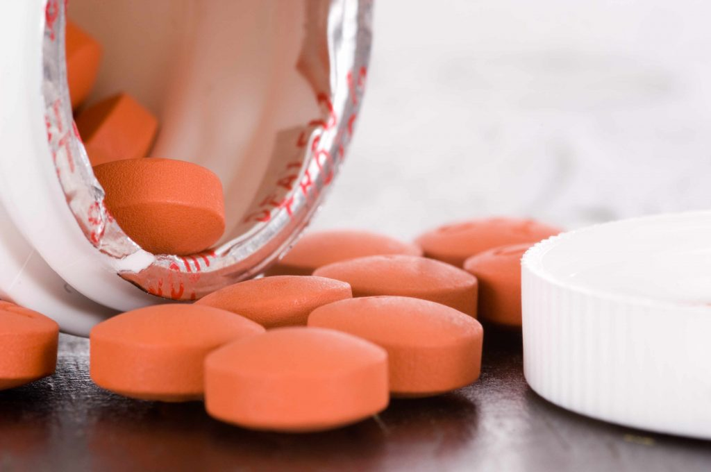 an open medication container spilling ibuprofen tablets out onto a table
