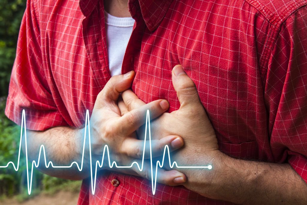 a man holding his chest in pain, perhaps having a heart attack