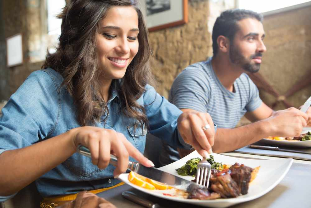 a young couple out to dinner with woman cutting food on her plate