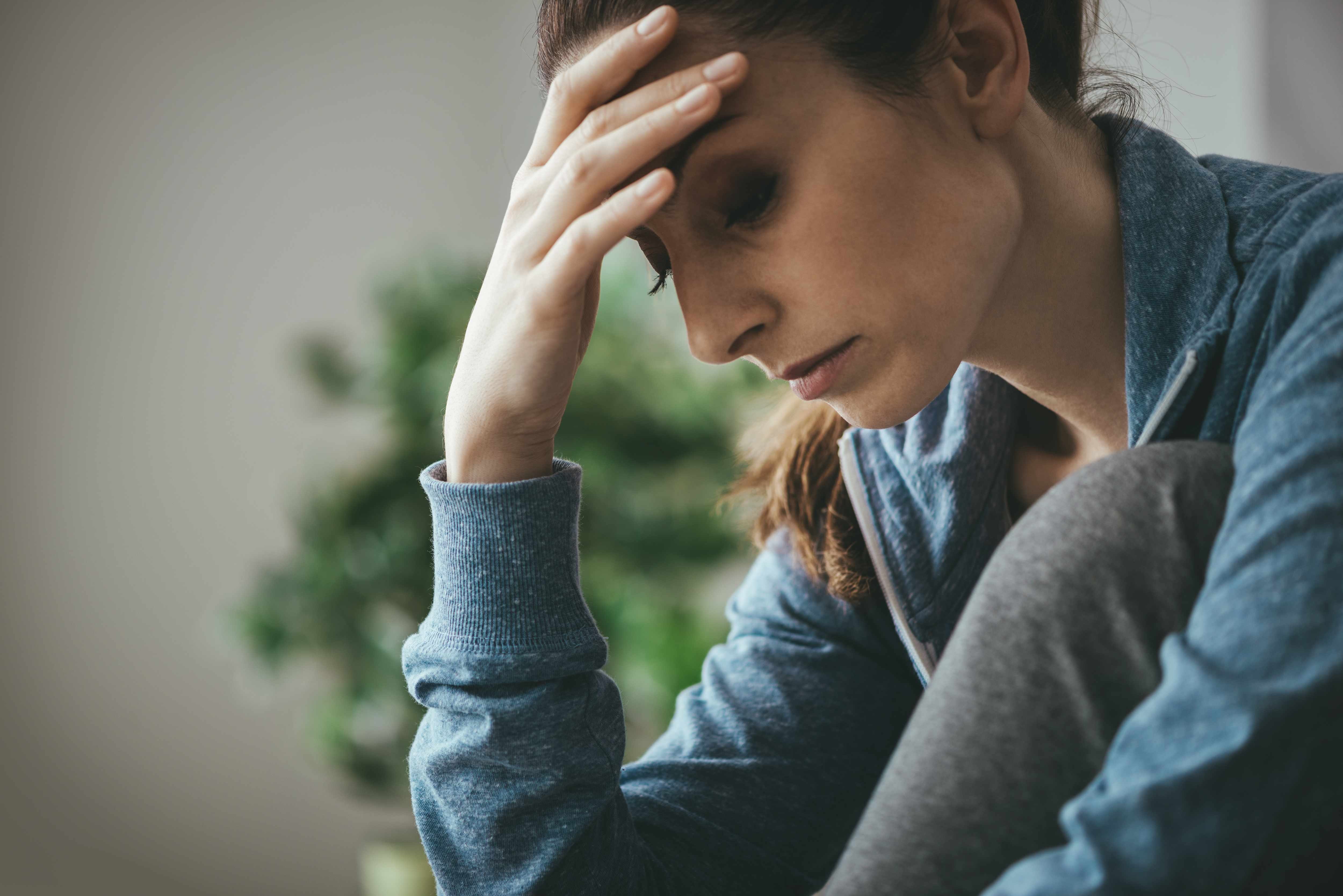 a woman resting her head in her hand looking sad and depressed, thinking negative thoughts