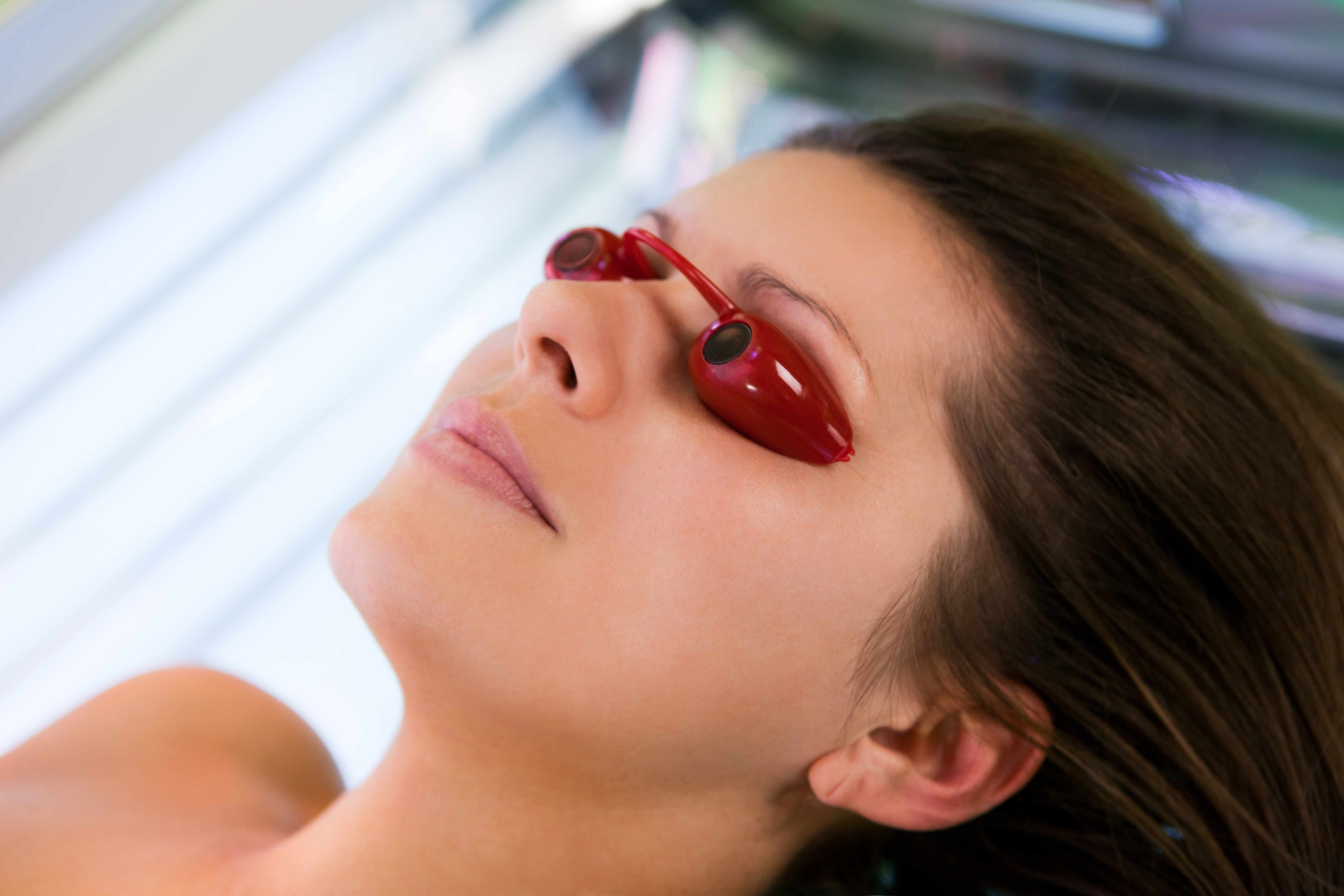 a young woman in tanning bed wearing eye protecting goggles