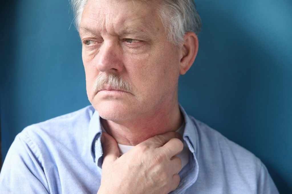 Un hombre con la mano sobre la garganta irritada, posiblemente sufre de ERGE con reflujo ácido y acidez estomacal