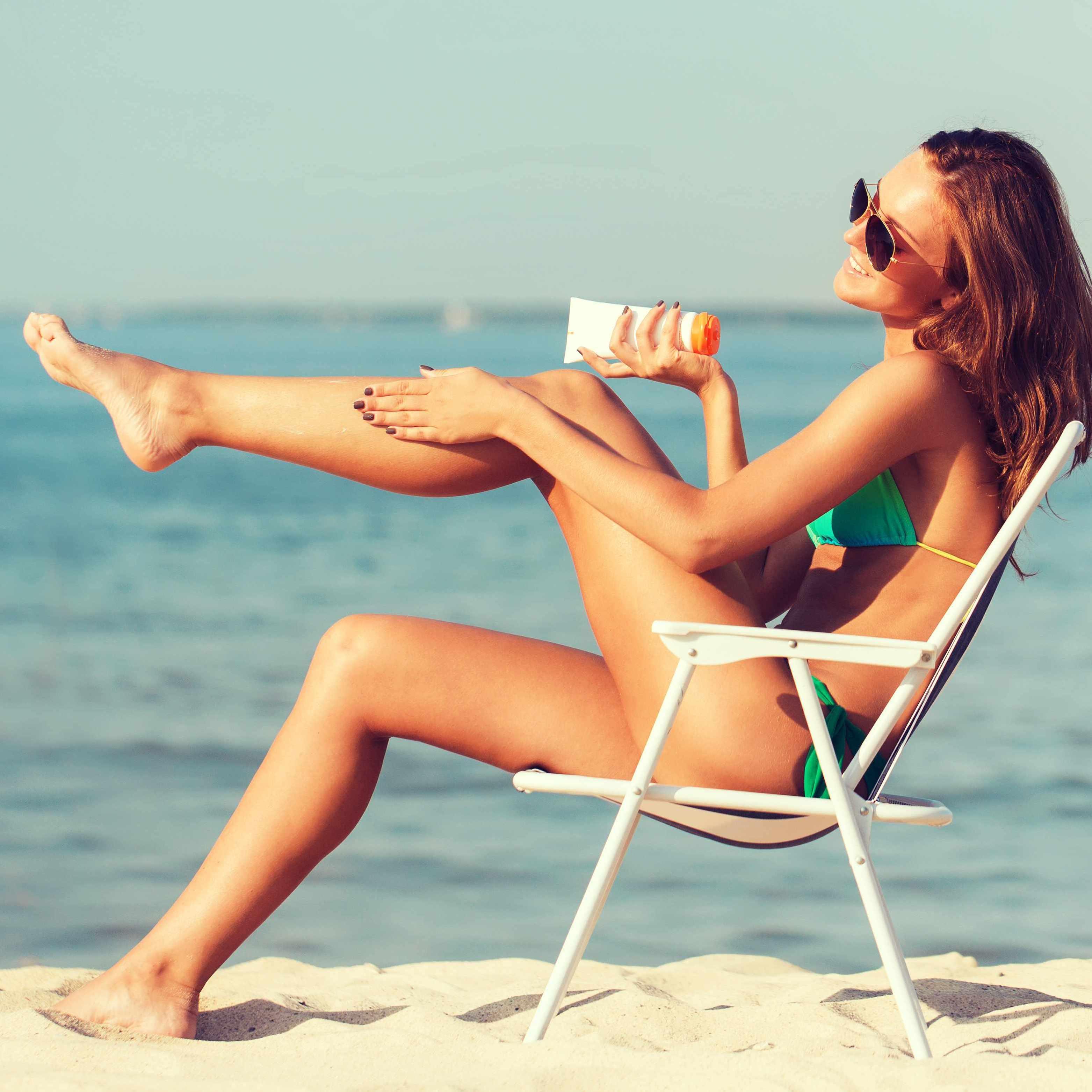 Women applying sun tan lotion and sunbathing on beach