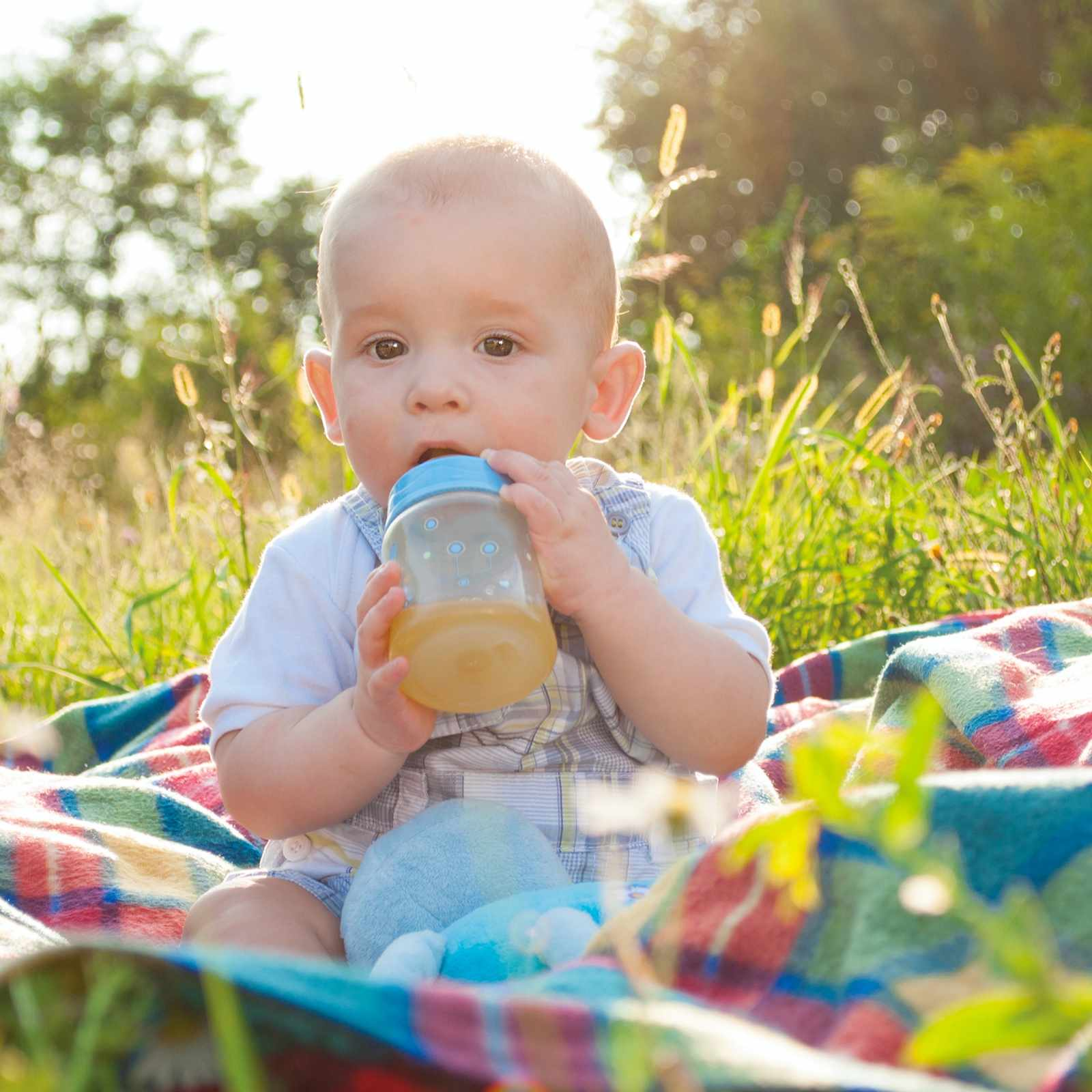 a baby sitting outside on a blanket drinking from a juice bottle