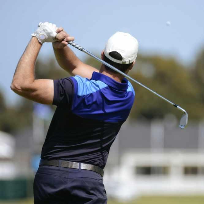 a golfer swinging and hitting a golf ball
