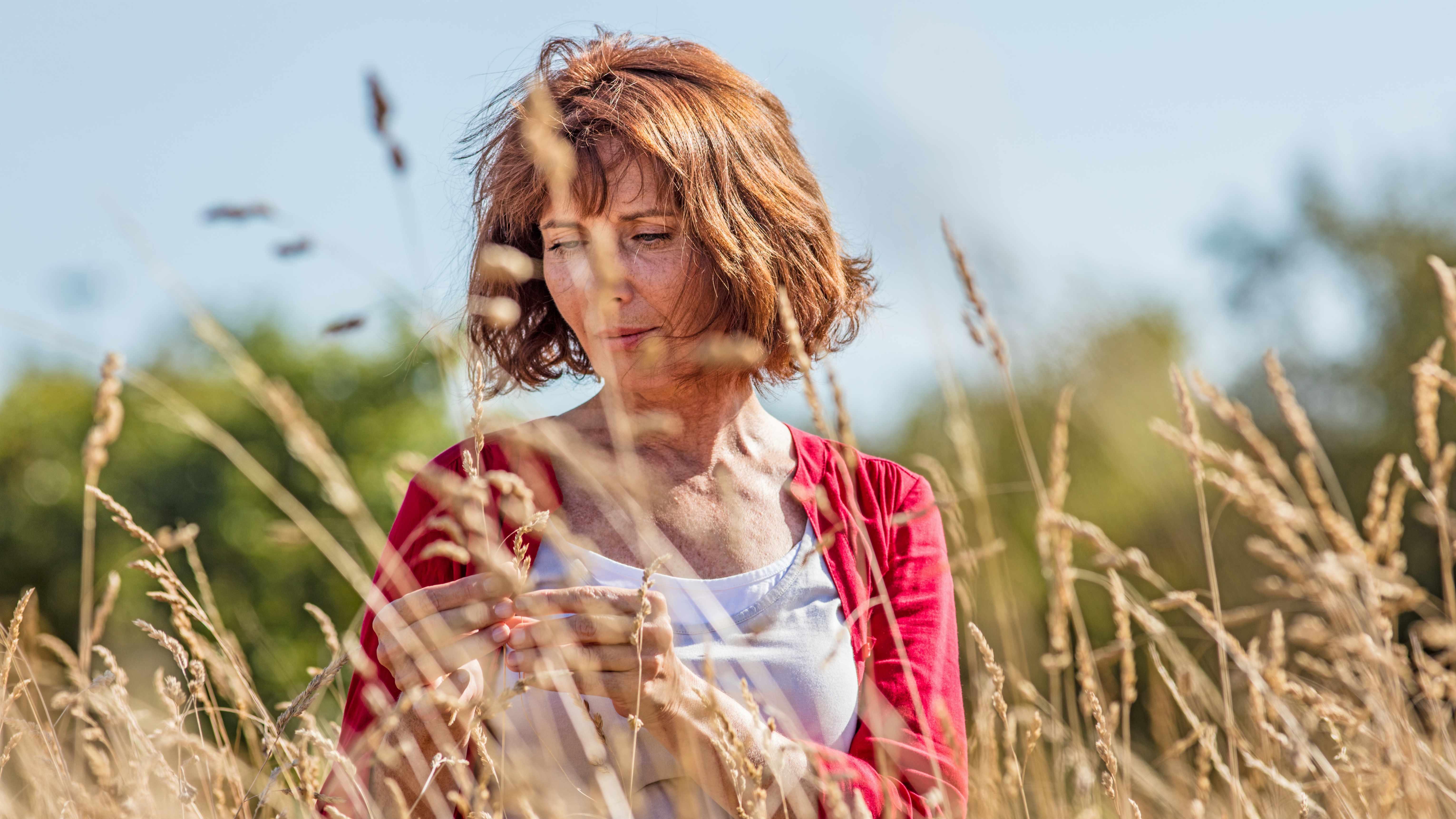 Mujer de mediana edad en un campo, pensativa y con la mirada seria