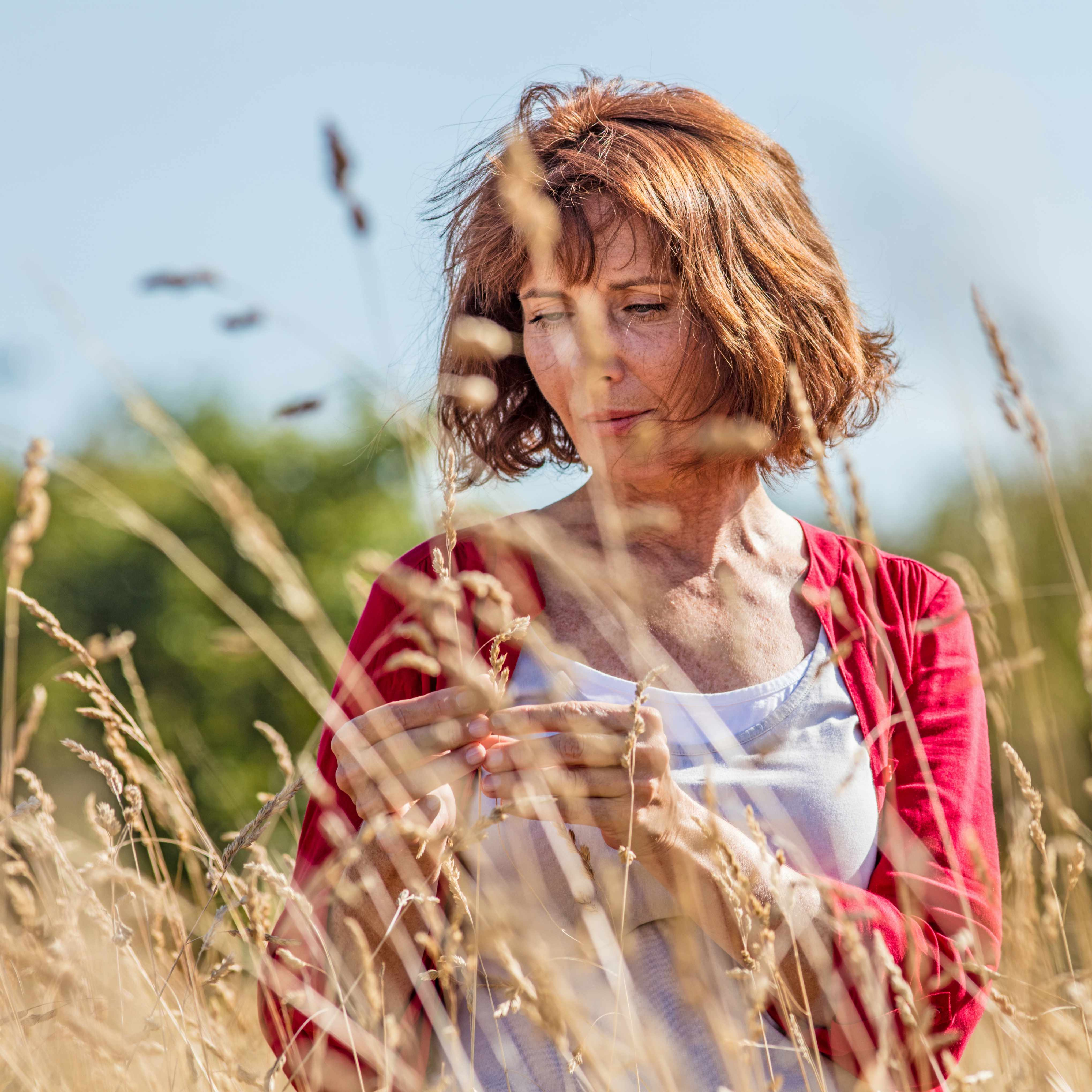 a middle-aged woman in a field of wheat taking a nature walk and looking serious or sad