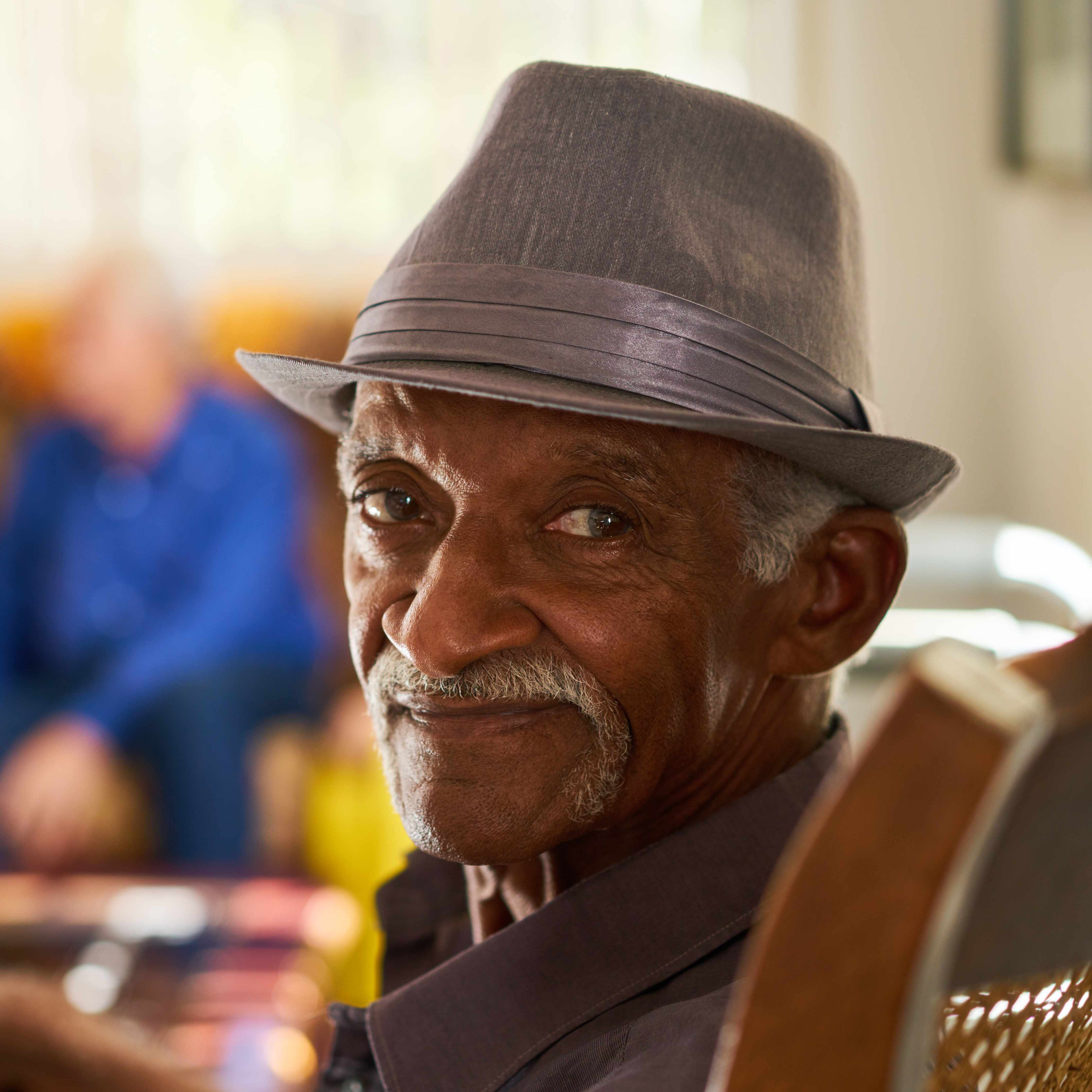 a smiling elderly man sitting in a chair at home