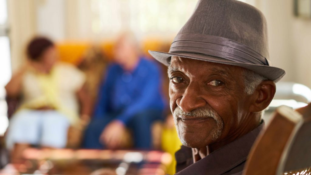 a smiling elderly man sitting in a chair at home, with two other people sitting on a couch talking in the background